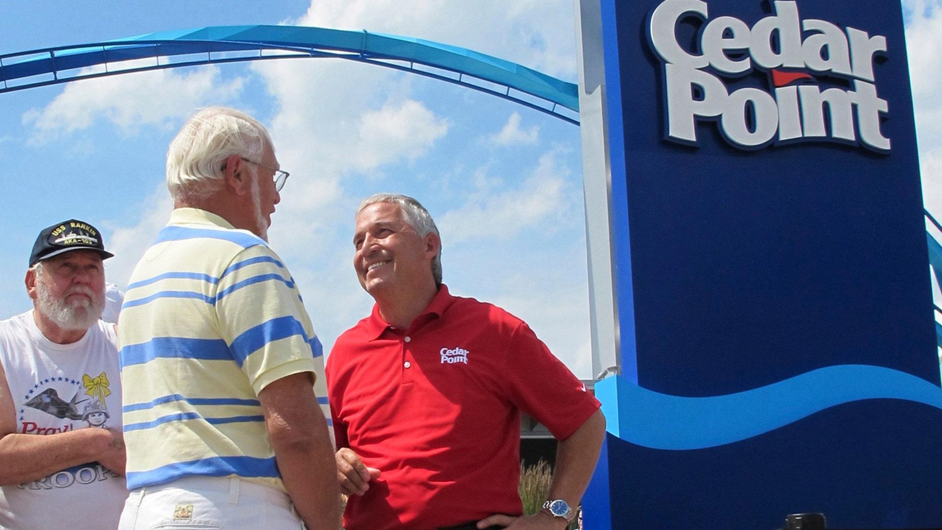 FILE - In this July 2, 2014, file photo, Matt Ouimet, chief executive of Cedar Fair Entertainment Co., greets a guest at Cedar Point amusement park, in Sandusky, Ohio.