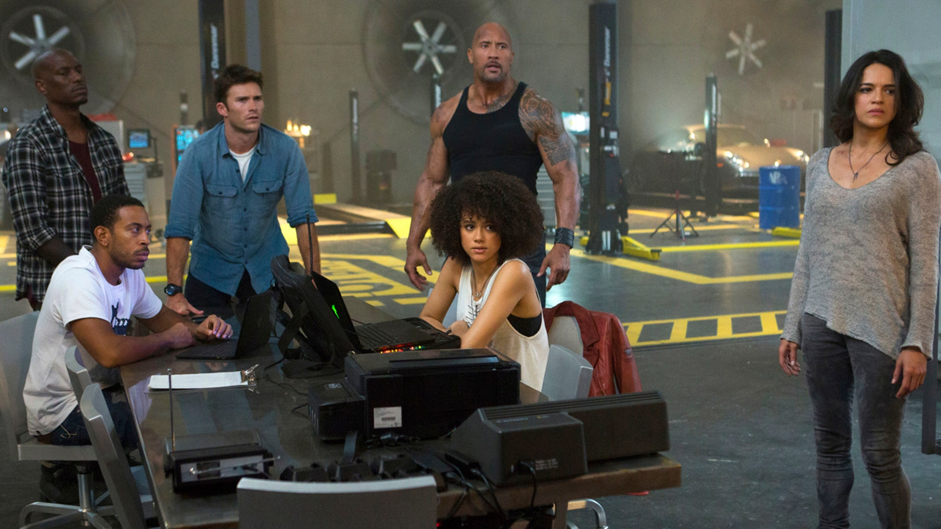"""This image released by Universal Pictures shows, Chris """"Ludacris"""" Bridges, seated left, and Nathalie Emmanuel, seated right, and Tyrese Gibson, standing from left, Scott Eastwood, Dwayne Johnson and Michelle Rodriguez in """"The Fate of the Furious."""""""