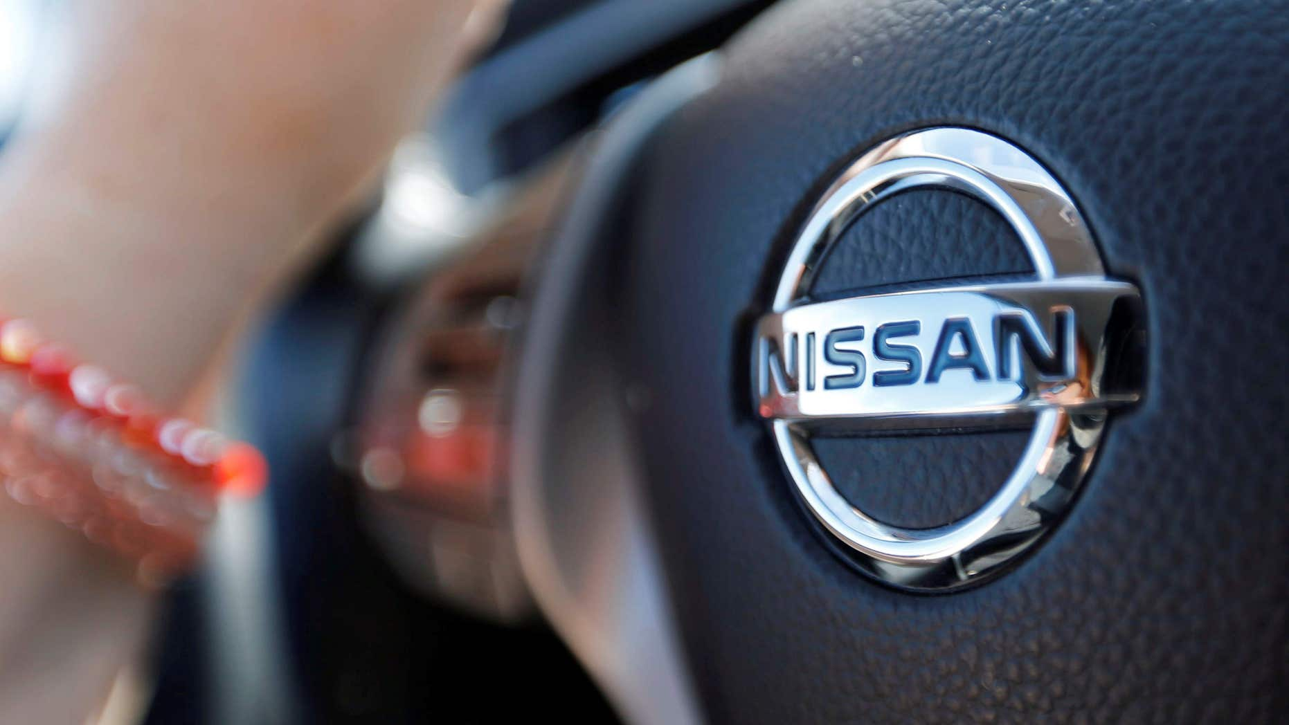 April 23, 2016: A logo of Nissan Motor Co is seen on a steering wheel as a woman drives her car in Golfech, southwestern France.