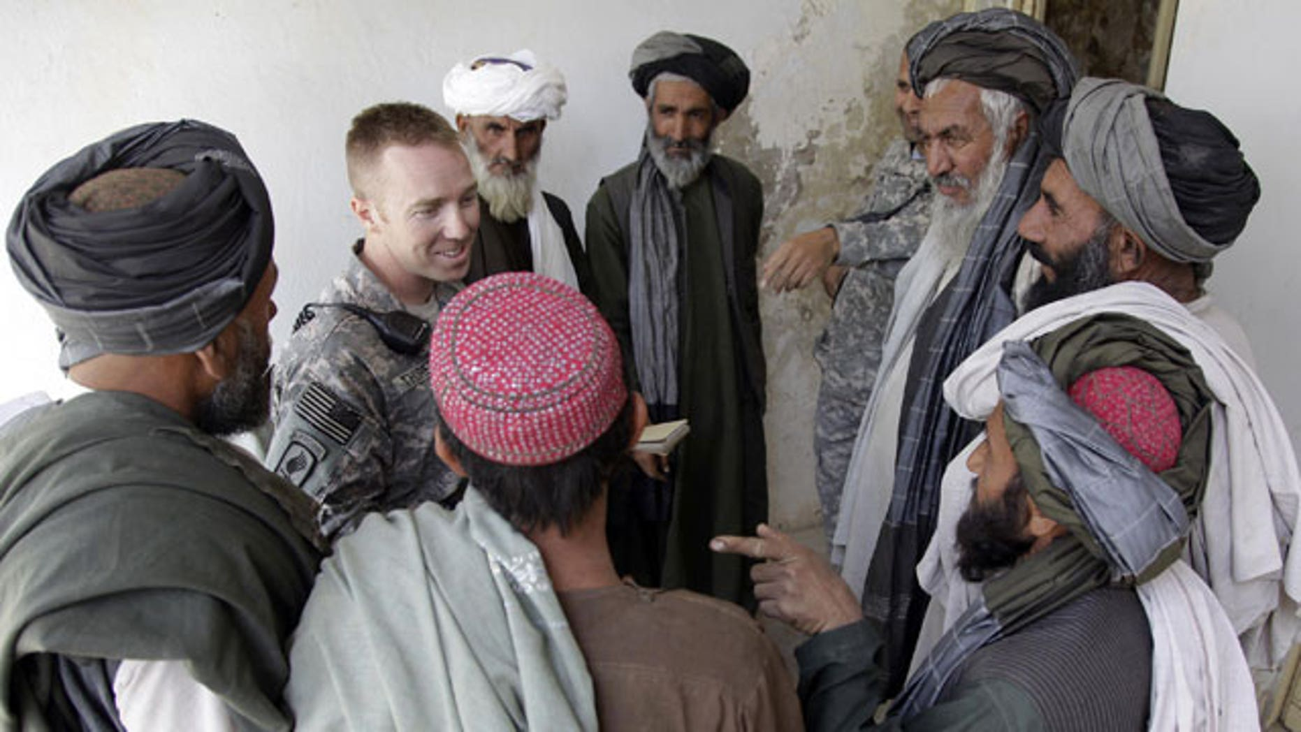 """In this Wednesday, April 28, 2010 photo, U.S. Army Capt. Casey Thoreen, second from left, of Seattle, Wash., Bravo Company, 2nd Battalion, 1st Infantry Regiment, 5th Stryker Brigade, talks with village leaders before the start of a shura , in the Maiwand district of Afghanistan's Kandahar province. To the locals, he is the """"King of Maiwand"""" district testimony to the fact that without the resources the young captain and others like him provide, local government in much of insurgency-ravaged southern Afghanistan could not function at all."""