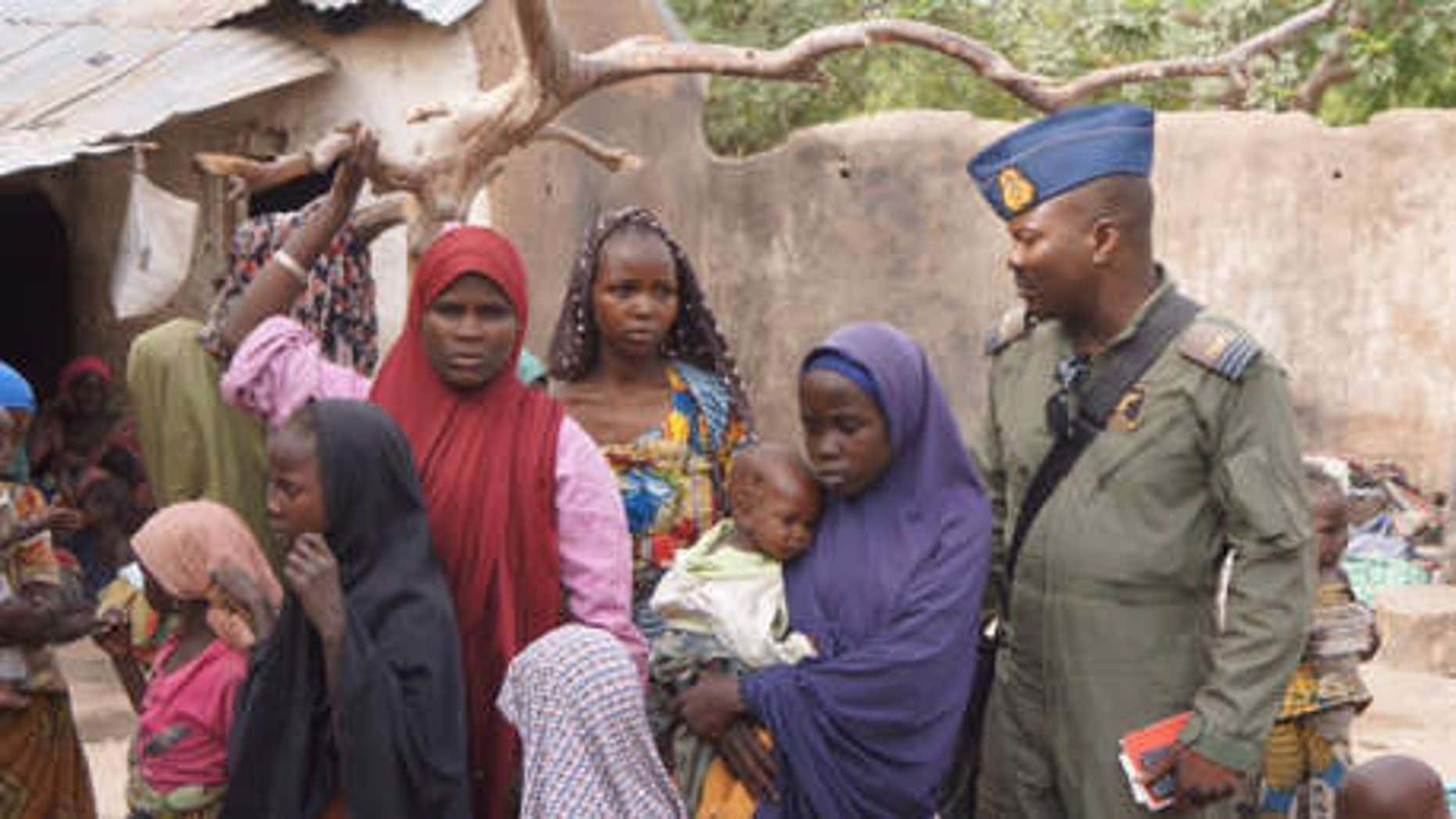 April 29, 2015: A Nigerian soldier stands next to woman and children that were allegedly rescued by the Nigerian Military after being taken by Islamic extremists in Sambisa Forest, Nigeria.