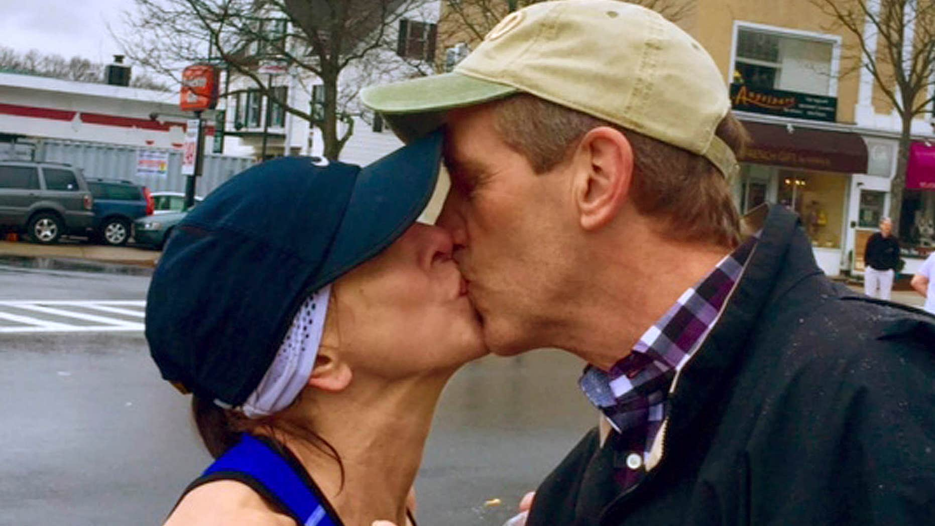 April 20, 2015: In this photo provided by Paige Tatge, her mother, Barbara Tatge, left, kisses an unknown spectator in Wellesley, Mass.