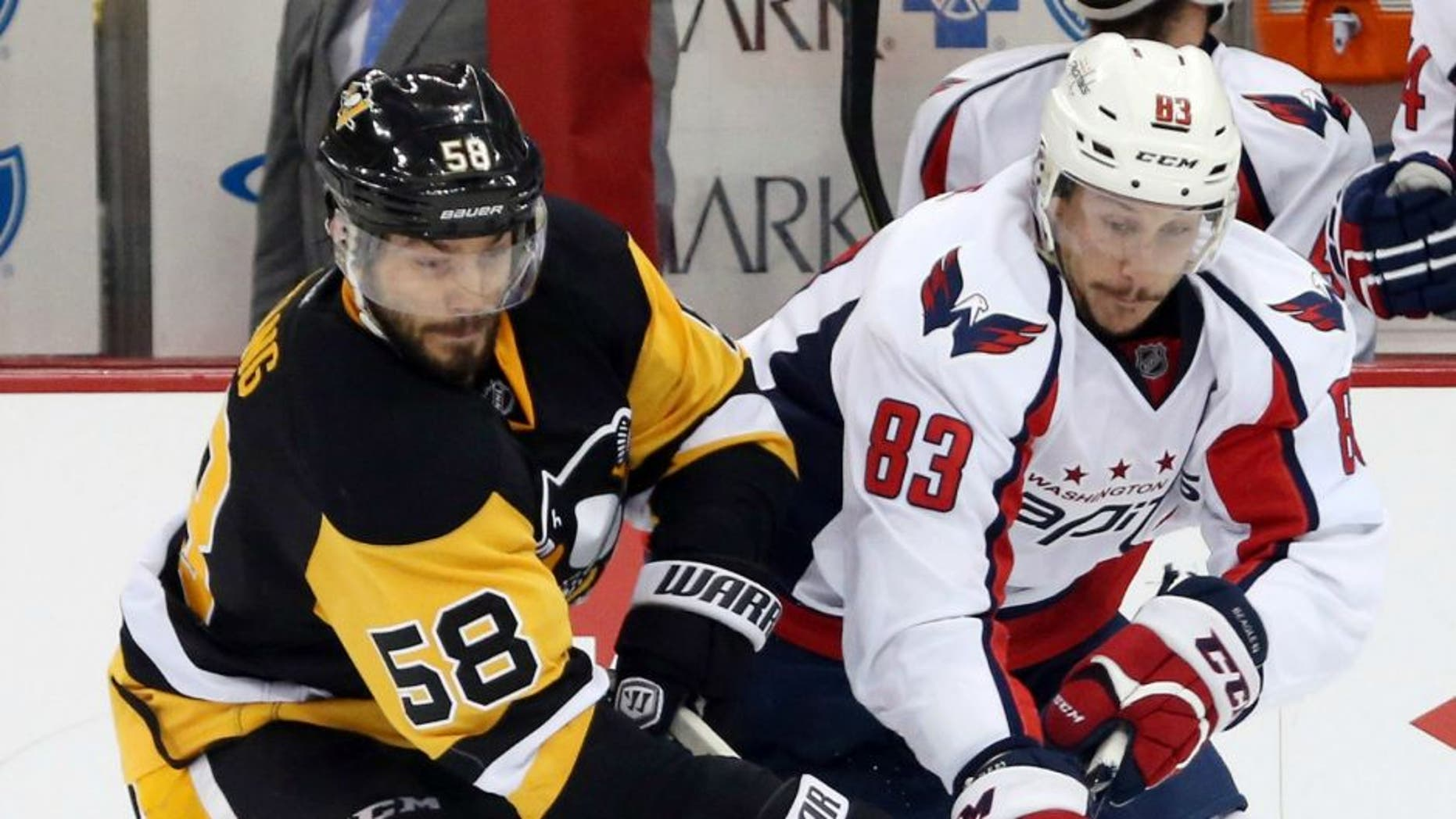 May 2, 2016; Pittsburgh, PA, USA; Pittsburgh Penguins defenseman Kris Letang (58) and Washington Capitals center Jay Beagle (83) chase the puck during the second period in game three of the second round of the 2016 Stanley Cup Playoffs at the CONSOL Energy Center. The Pens won 3-2. Mandatory Credit: Charles LeClaire-USA TODAY Sports