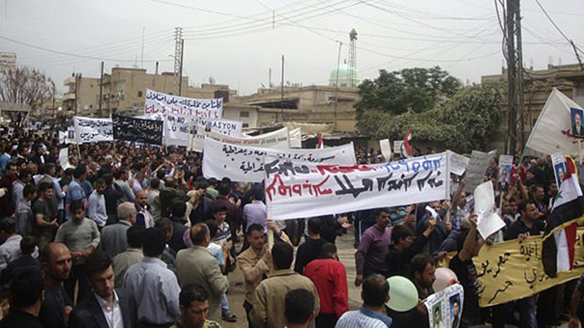 In this citizen journalism image made on a mobile phone and acquired by the AP, Syrian protesters carry banners in Arabic and Kurdish that call for a democratic nation as they demonstrate in the northeastern town of Qamishli, Syria, Friday, April 29, 2011.