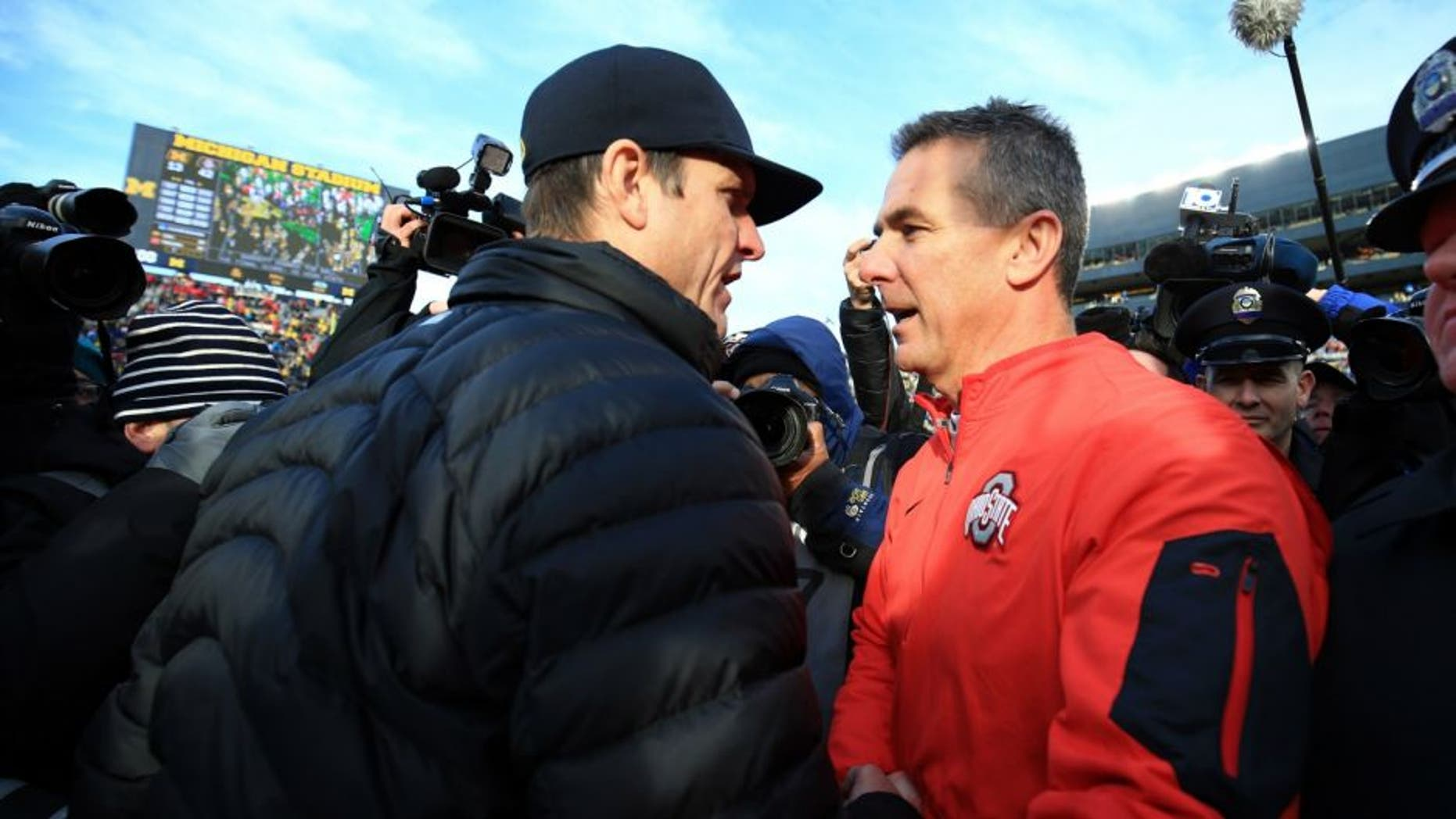 ANN ARBOR, MI - NOVEMBER 28: Head coach Urban Meyer of the Ohio State Buckeyes and head coach Jim Harbaugh of the Michigan Wolverines after the game against the Michigan Wolverines at Michigan Stadium on November 28, 2015 in Ann Arbor, Michigan. Ohio State defeated Michigan 42-13. (Photo by Andrew Weber/Getty Images) *** Local Caption *** Urban Meyer; Jim Harbaugh