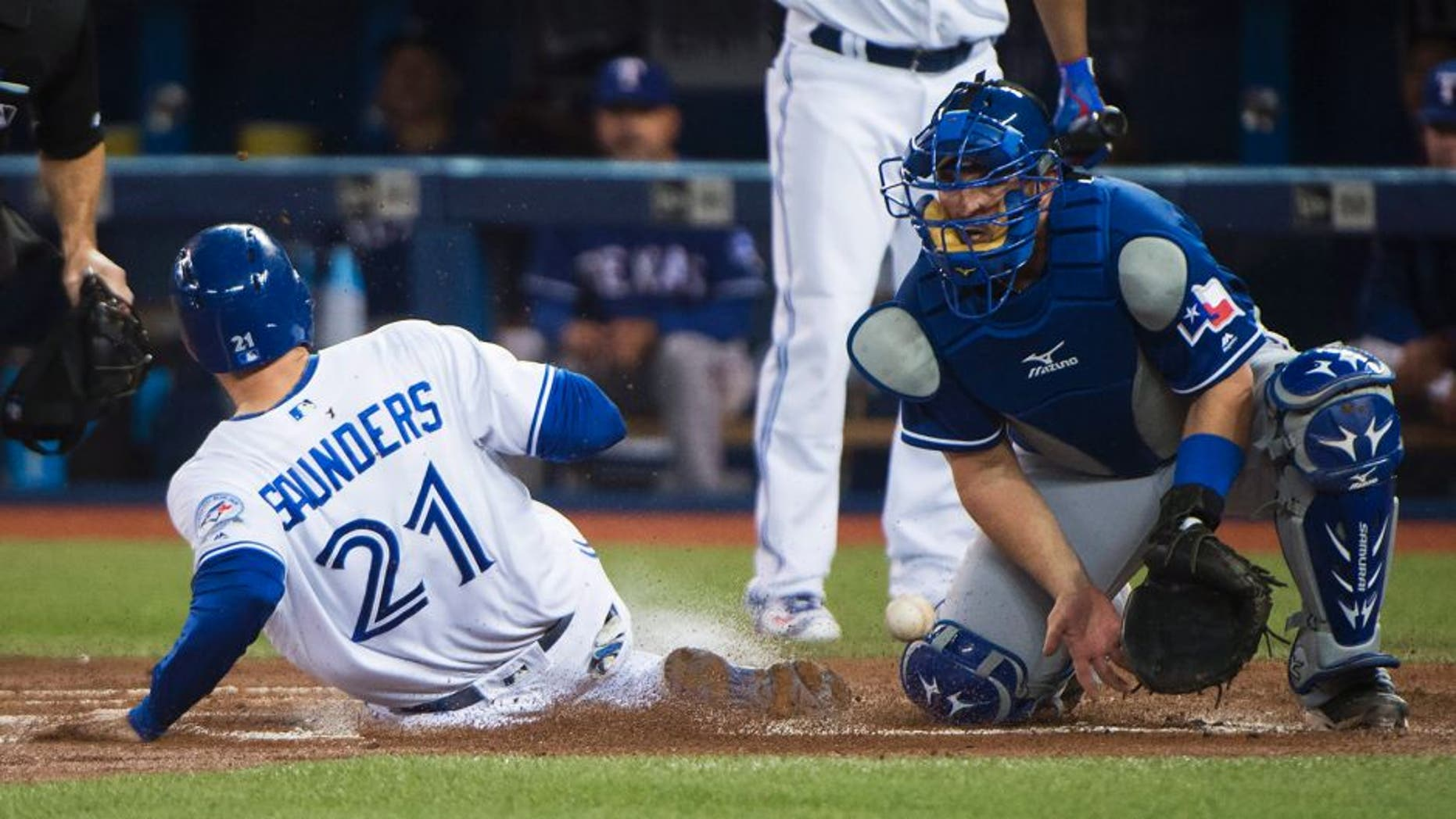Toronto Blue Jays left fielder Michael Saunders (21) sides safe at home plate past Texas Rangers catcher Bobby Wilson, right, during the first inning of a baseball game, Wednesday, May 4, 2016, 2016 in Toronto. (Nathan Denette/The Canadian Press via AP) MANDATORY CREDIT