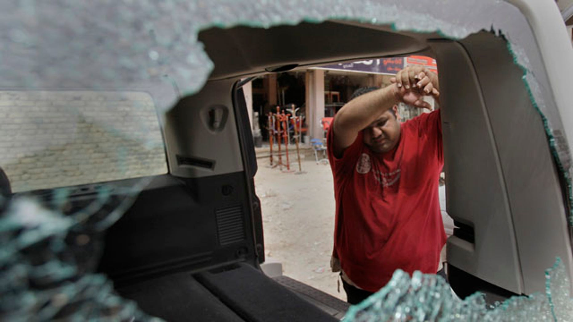 An Iraqi man inspects his damaged car at the site of a roadside bomb attack targeting a police patrol, killing and wounding a few civilians, police said, in central Baghdad, Iraq, Thursday, May 5, 2011. (AP Photo/Khalid Mohammed)