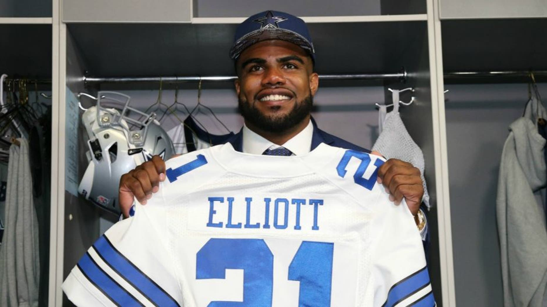 Apr 29, 2016; Irving, TX, USA; Dallas Cowboys number one draft pick Ezekiel Elliott holds his jersey in the locker room at Dallas Cowboys Headquarters Mandatory Credit: Matthew Emmons-USA TODAY Sports