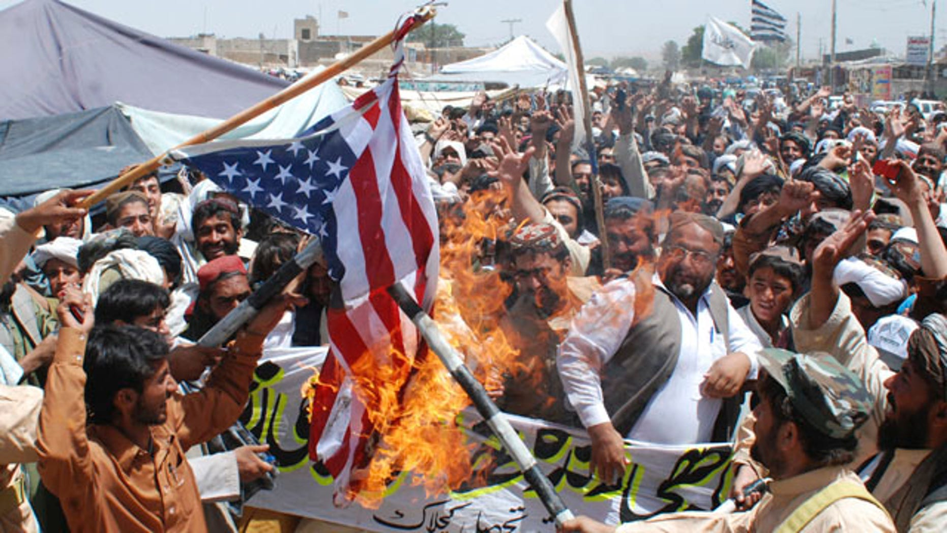 May 6: Supporters of Pakistani religious party Jamiat Ulema-e-Islam burn representation of a U. S. flag during a rally to condemn the killing of Al Qaeda leader Usama bin Laden, in Kuchlak, Pakistan.