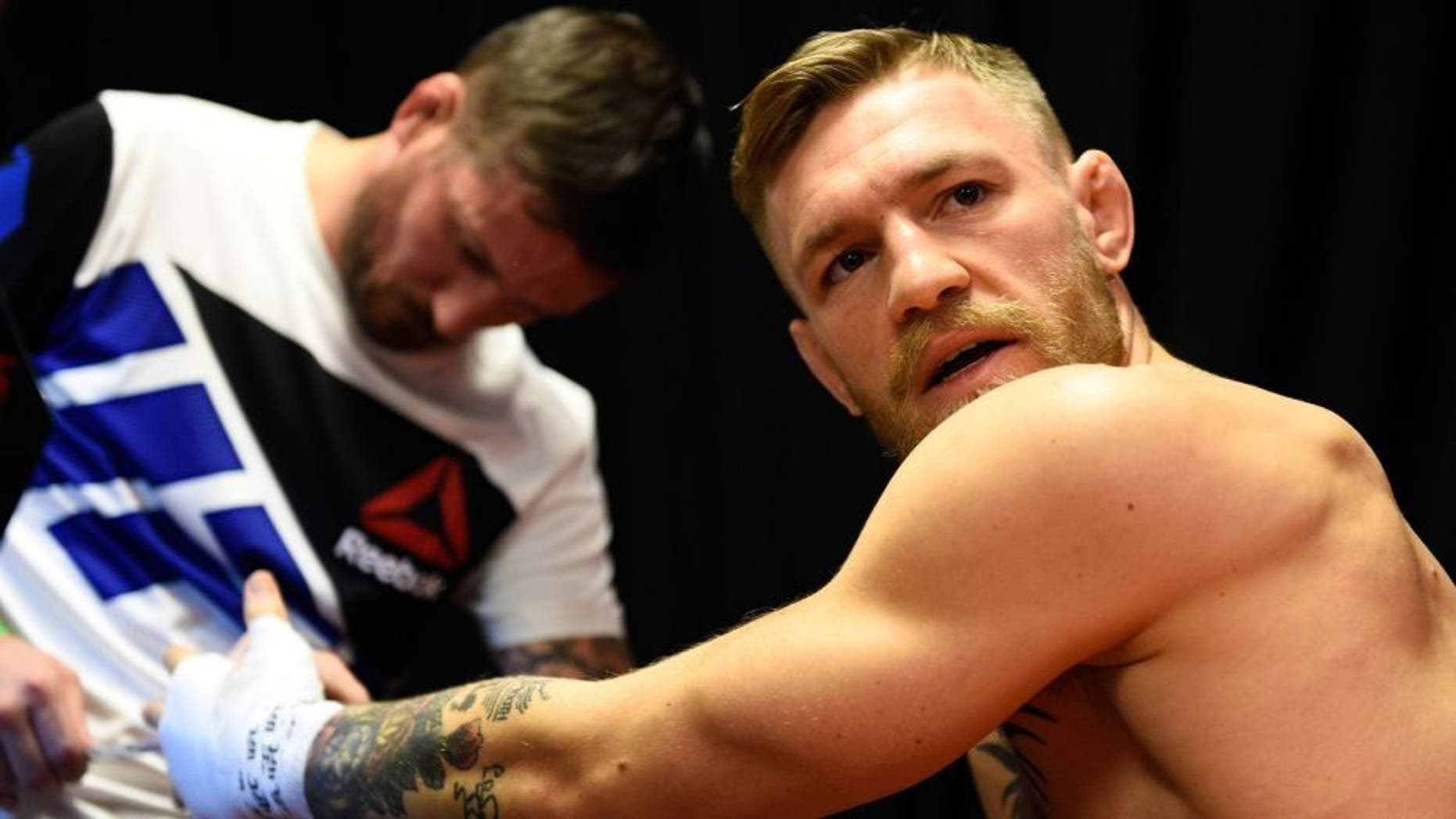 LAS VEGAS, NEVADA - DECEMBER 12: (R-L) Conor McGregor of Ireland gets his hands wrapped by coach John Kavanaugh backstage during the UFC 194 event inside MGM Grand Garden Arena on December 12, 2015 in Las Vegas, Nevada. (Photo by Jeff Bottari/Zuffa LLC/Zuffa LLC via Getty Images)