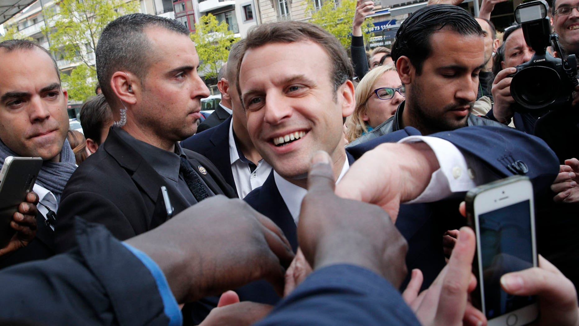 French independent centrist presidential candidate Emmanuel Macron shakes hands to supporters as he campaigns in Rodez, southern France, Friday, May 5, 2017.