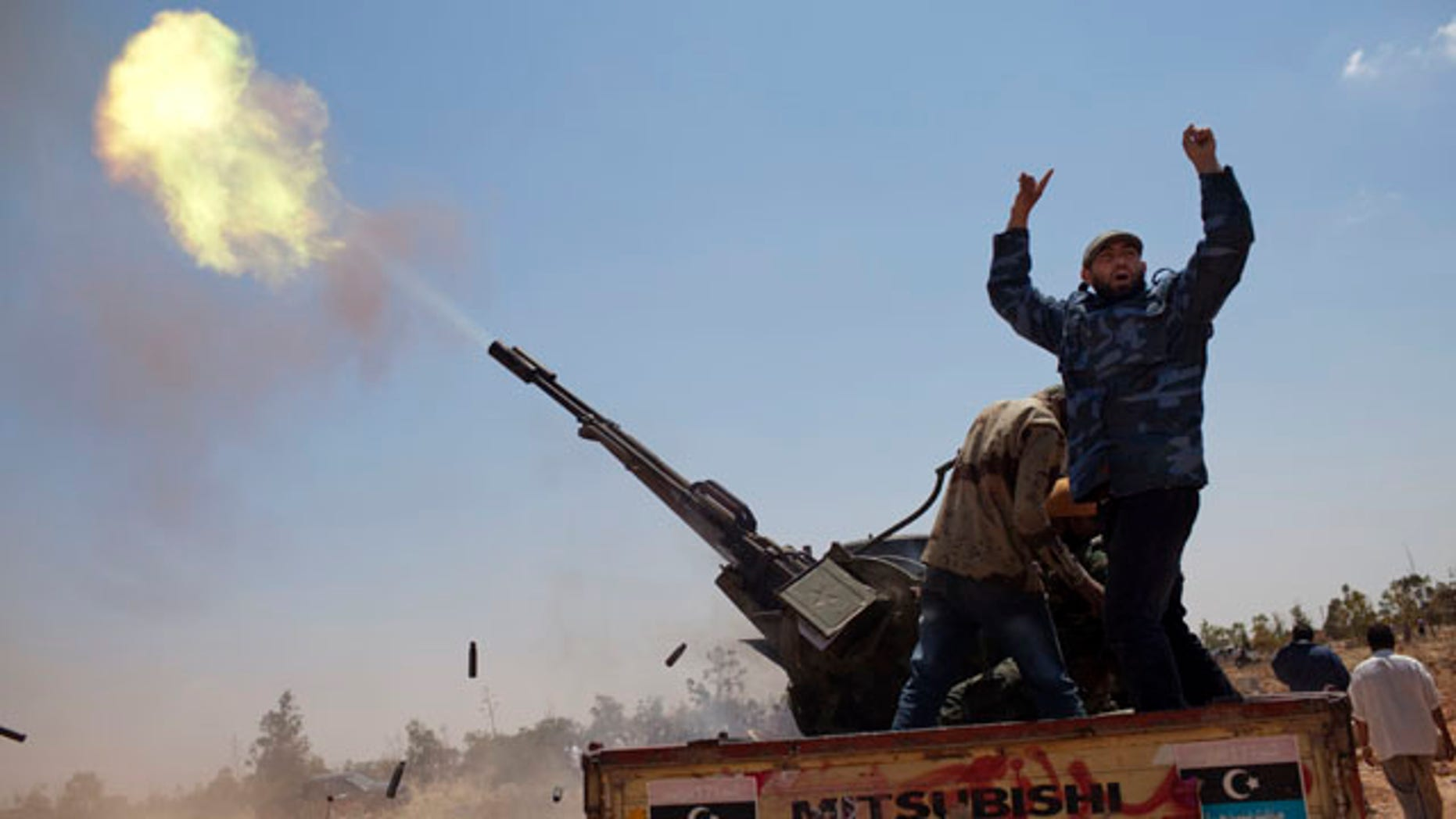 May 7: A rebel fighter gestures as an anti-aircraft gun fires into the sky in a gesture to salute the dead, during the funeral of three rebel fighters killed by Muammar al-Qaddafi forces,  Benghazi, Libya.