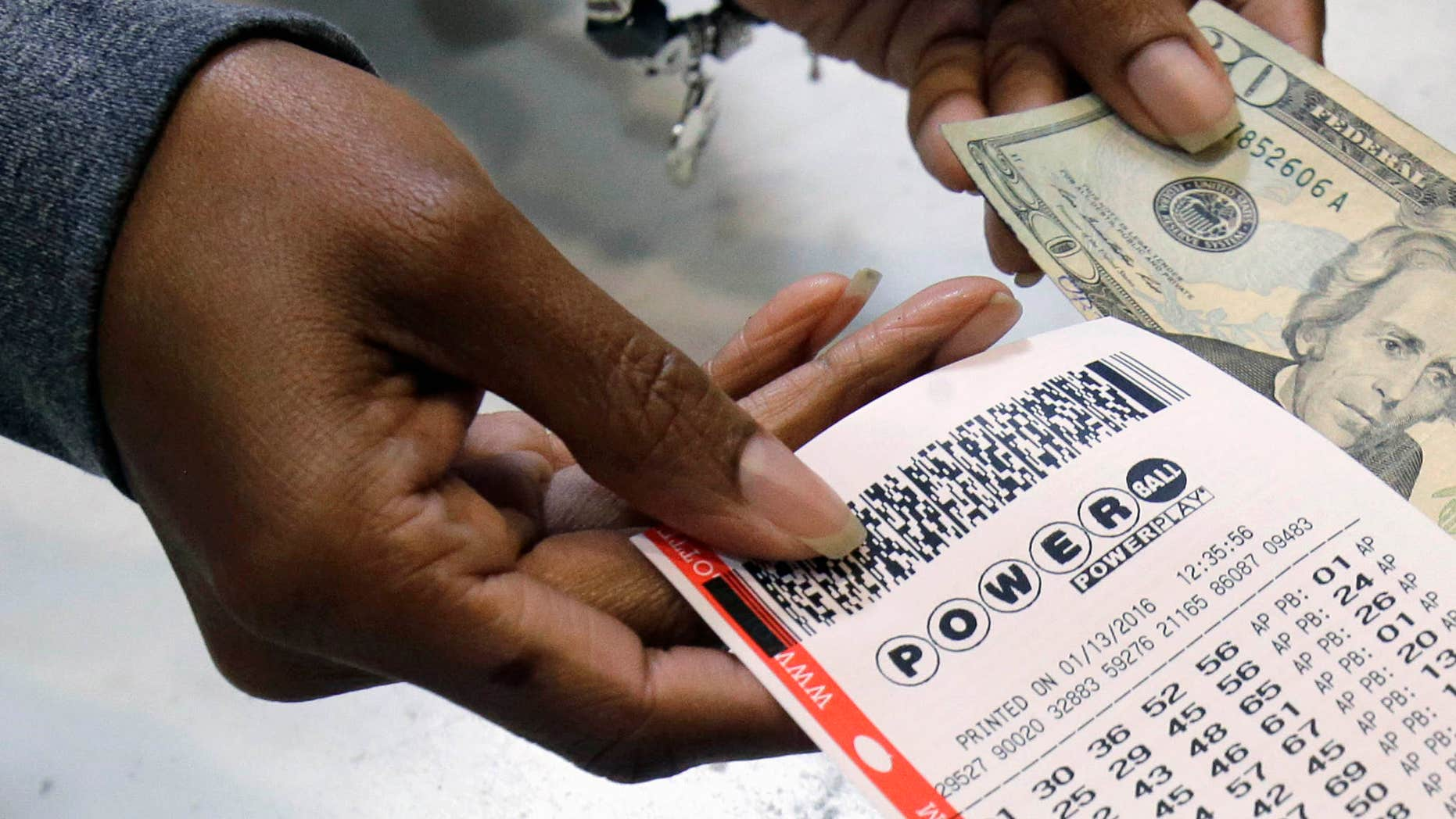 FILE - In this Jan. 13, 2016 file photo, a clerk hands over a Powerball ticket for cash at Tower City Lottery Stop in Cleveland.