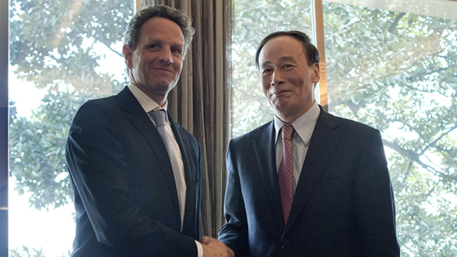 In this March 31, 2011, file photo U.S. Treasury Secretary Timothy Geithner, left, shakes hands with Chinese Vice Premier Wang Qishan prior to having lunch on the sidelines of the G-20 High Level Seminar on the international monetary system in Nanjing, China.