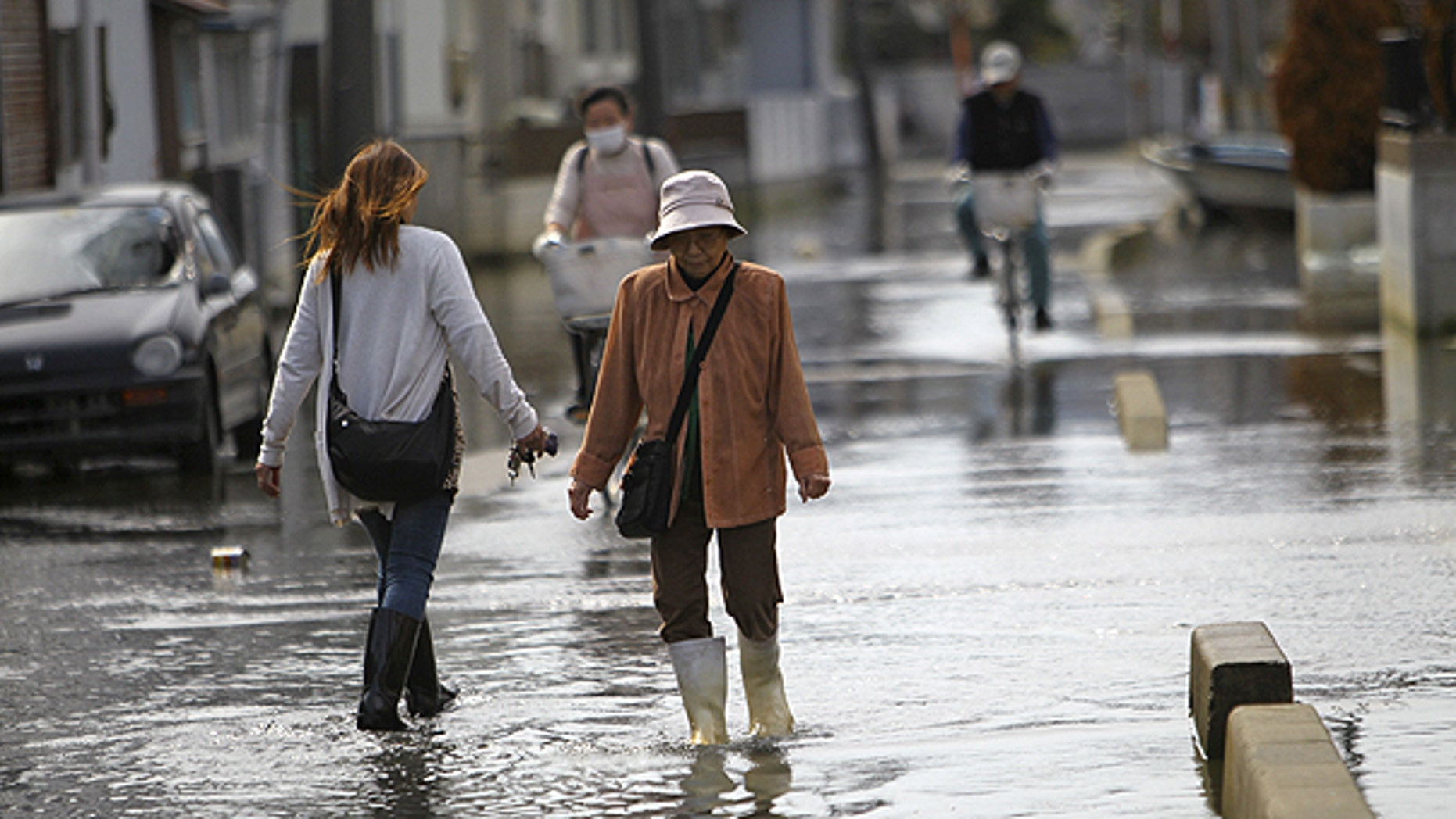 May 3: esidents stroll in a flooded street in Ishinomaki, Miyagi Prefecture, Japan. The area in this part of the city sunk nearly 2 feet 7 inches (0.8 meter) following the March 11 earthquake and tsunami.