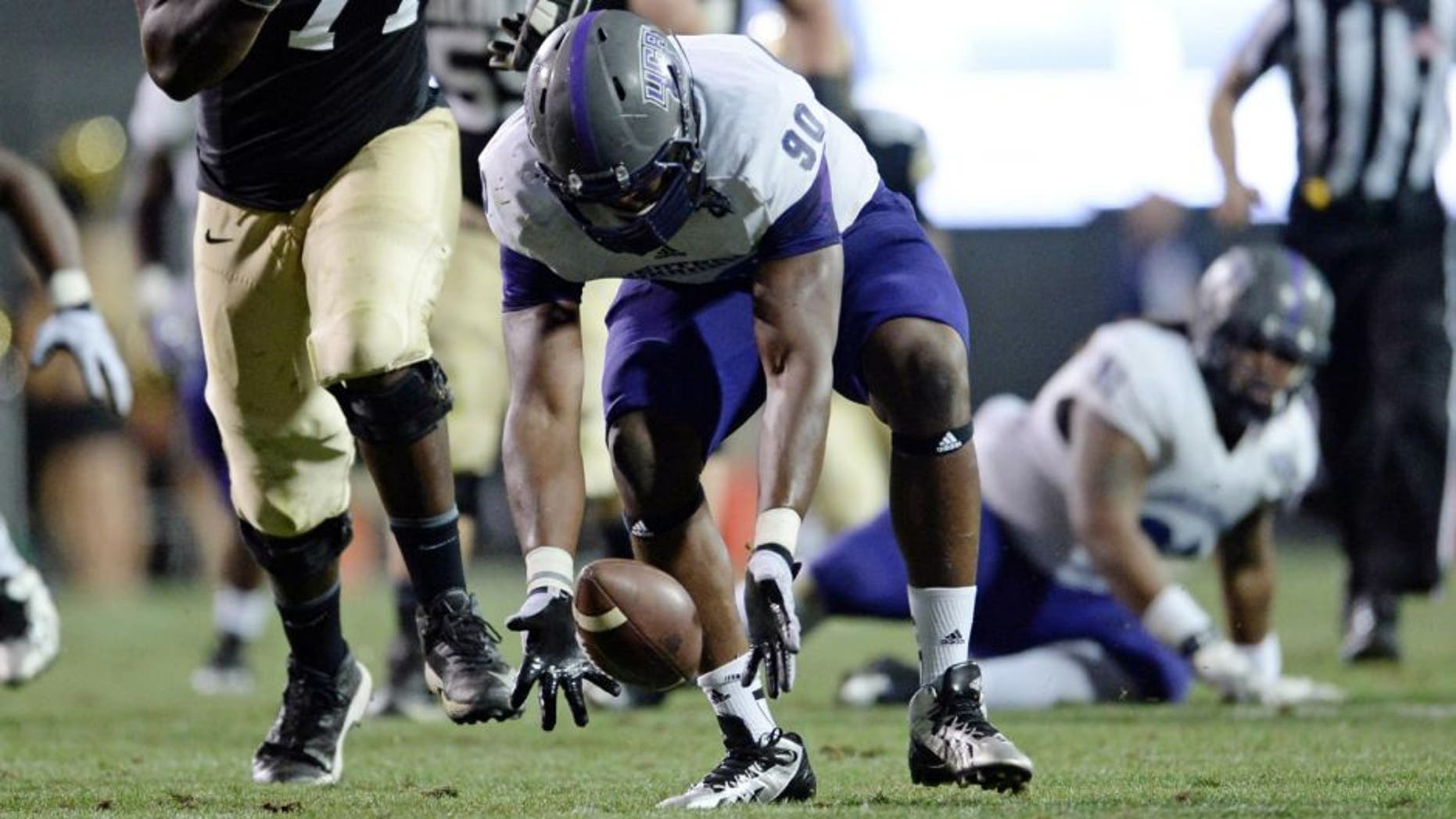 Sep 7, 2013; Boulder, CO, USA; Colorado Buffaloes offensive linesman Stephane Nembot (77) watches as Central Arkansas Bears defensive end Jonathan Woodard (90) chases down a fumble made by quarterback Connor Wood (not pictured) in the third quarter at Folsom Field. The Buffaloes defeated the Bears 38-24. Mandatory Credit: Ron Chenoy-USA TODAY Sports