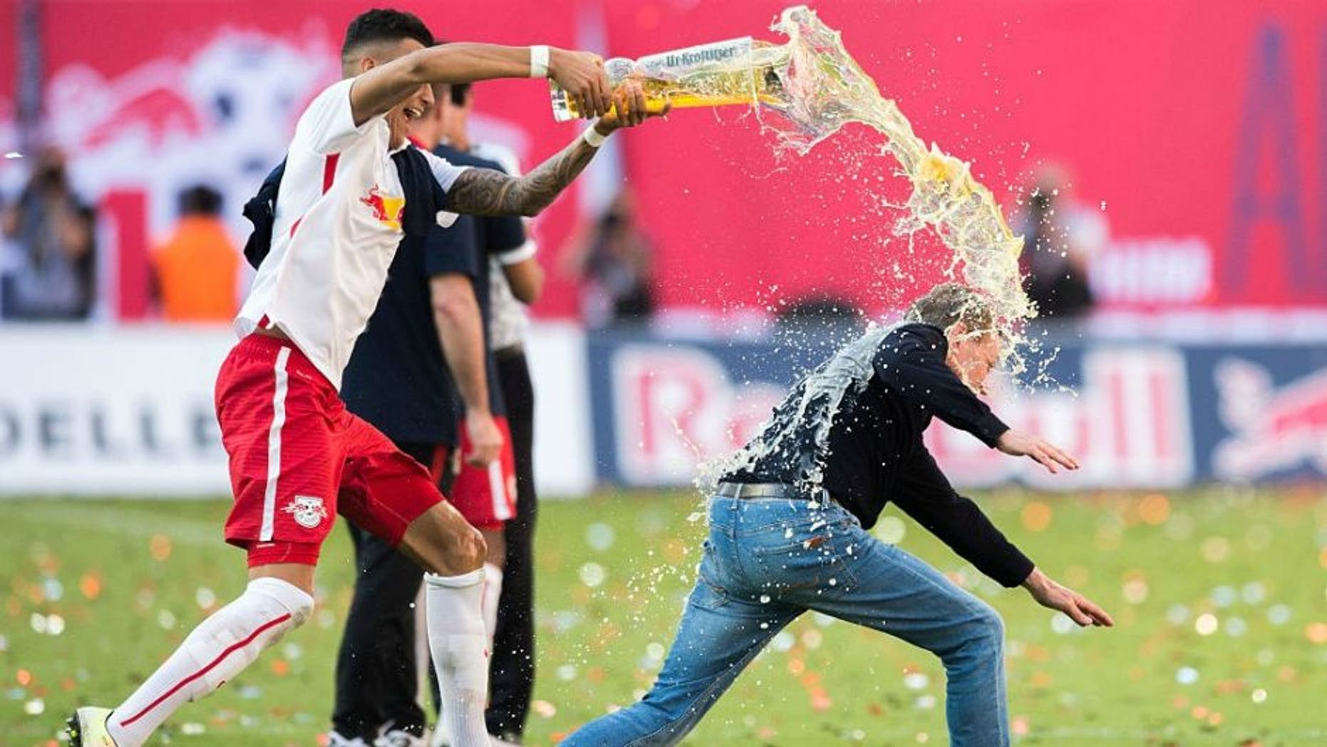 Leipzig��s Davie Selke (L) pours beer over headcoach Ralf Rangnick after the German second division Bundesliga football match between RB Leipzig and Karlsruher SC at the Red Bull Arena in Leipzig, eastern Germany, on May 8, 2016. Leipzig won the match 2-0 and will be promoted to the first division Bundesliga next season. / AFP / Robert MICHAEL (Photo credit should read ROBERT MICHAEL/AFP/Getty Images)