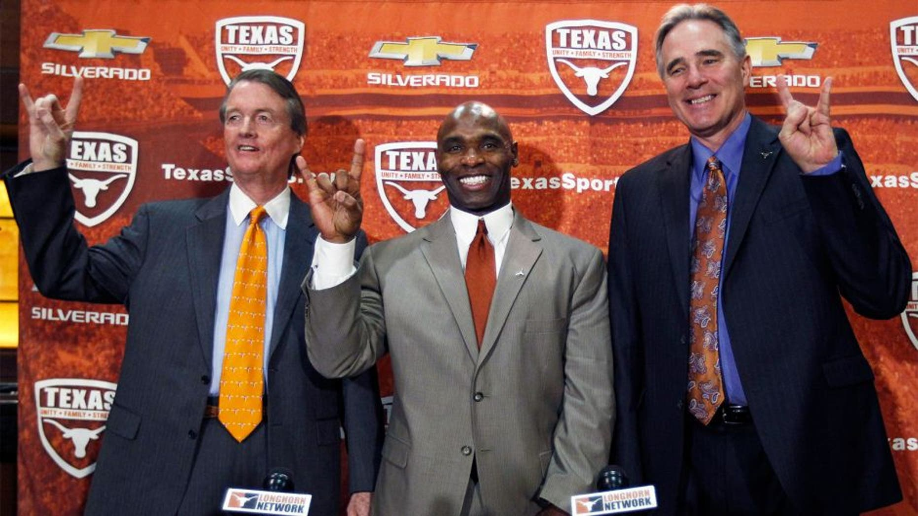 AUSTIN, TX - JANUARY 6: University of Texas president Bill Powers, left and athletic director Steve Patterson, right, introduce new Longhorns head football coach Charlie Strong from Louisville during a press conference January 6, 2014 at Darrell K. Royal-Texas Memorial Stadium in Austin, Texas. (Photo by Erich Schlegel/Getty Images)
