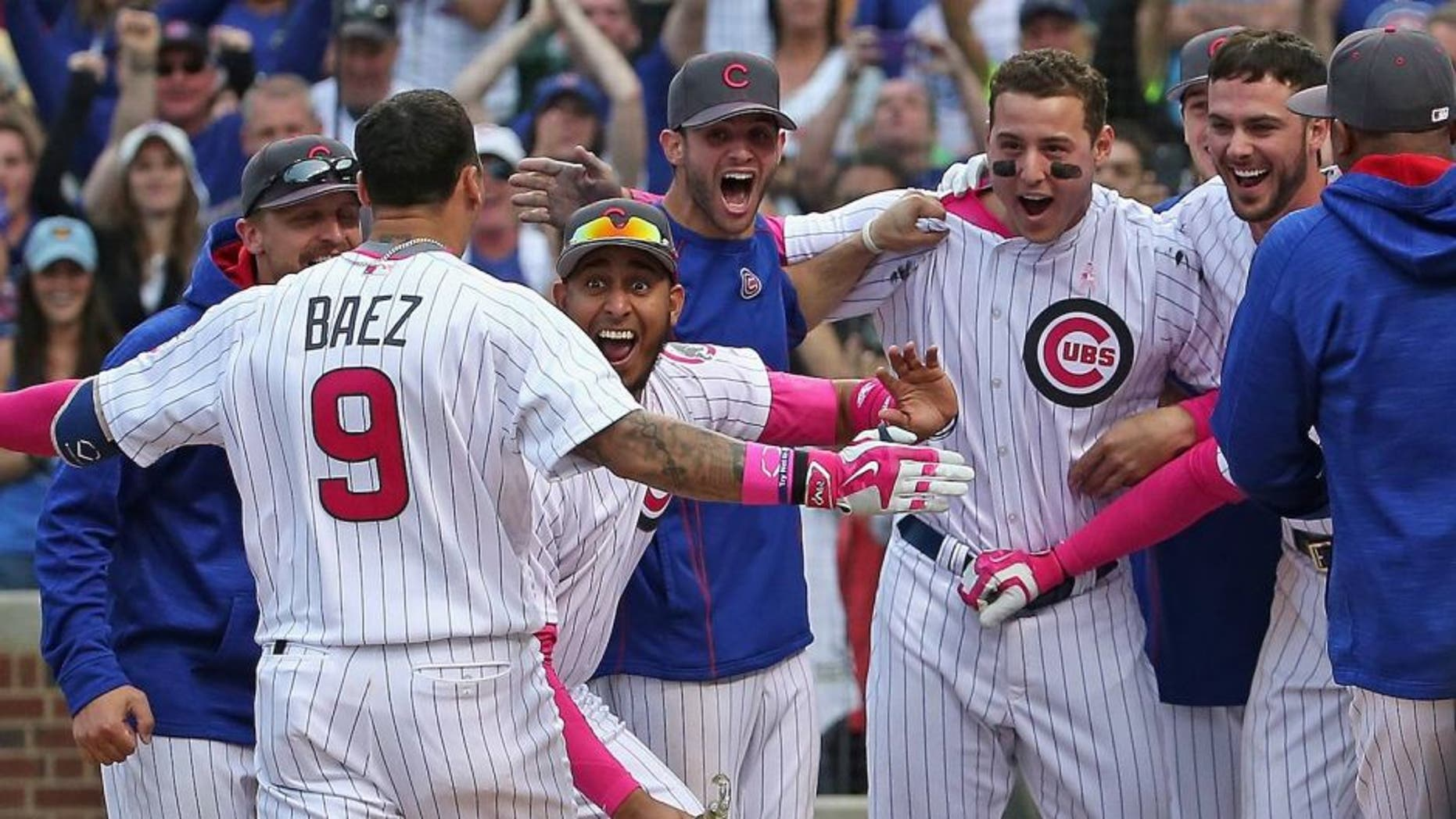 CHICAGO, IL - MAY 08: Javier Baez #9 of the Chicago Cubs is greeted by teammates after hitting the game-winning, walk off home run against the Washington Nationals at Wrigley Field on May 8, 2016 in Chicago, Illinois. The Cubs defeated the Nationals 4-3 in 13 innings. (Photo by Jonathan Daniel/Getty Images)