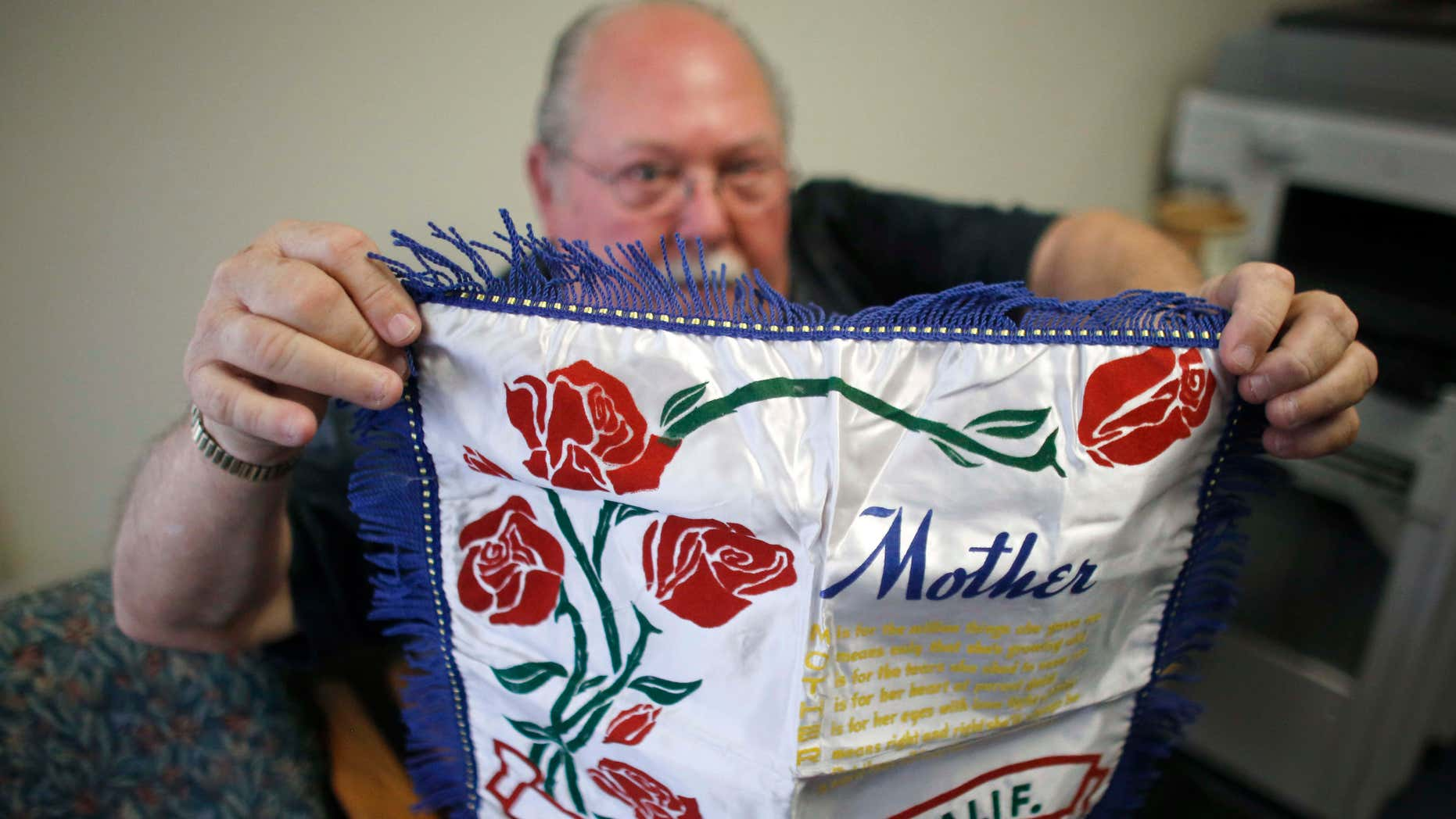 May 5, 2015: Don Lamoureux displays a World War II era pillow sham at a senior center in Millville, Mass., which his son purchased from an online auction site.
