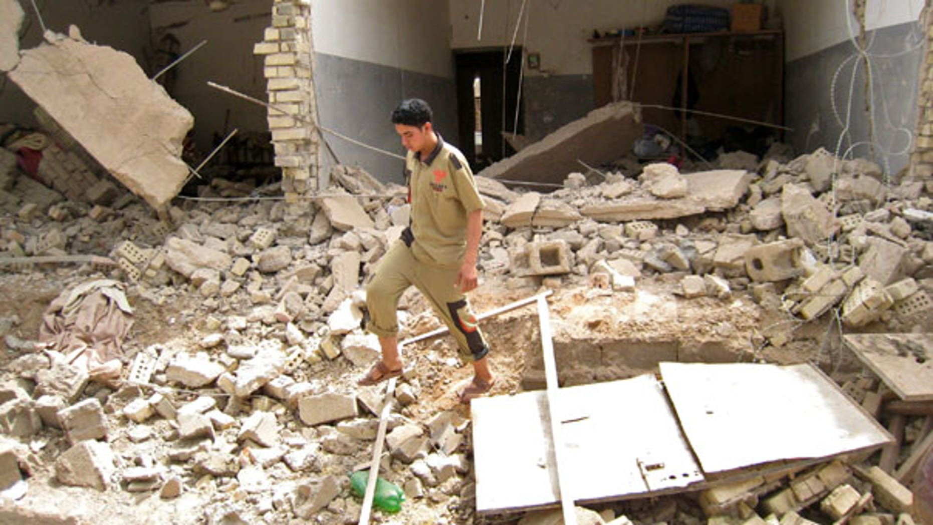 May 10: An Iraqi man walks through rubble at the site of a bombing that targeted police in Fallujah, Iraq (AP).