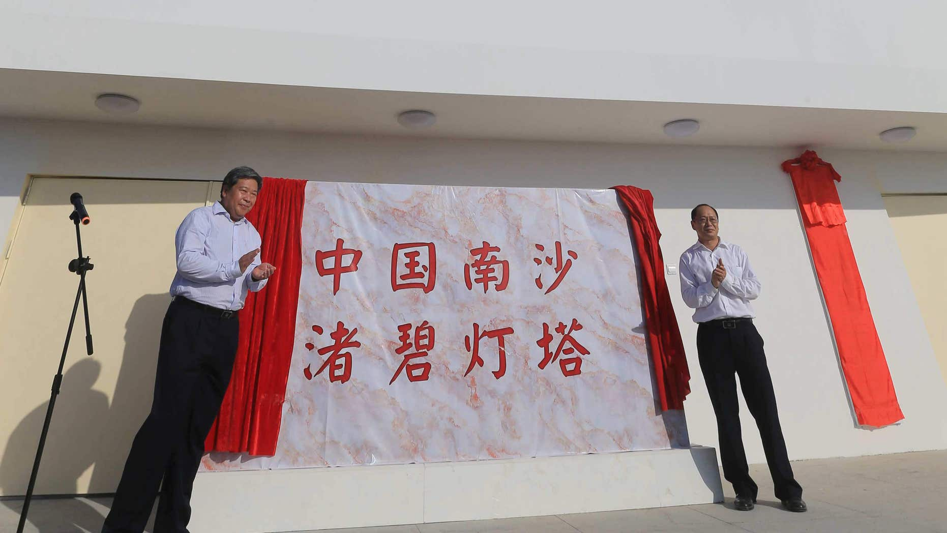 FILE - In this April 5, 2016 file photo provided by China's Xinhua News Agency, guests attend the completion ceremony for the construction of a lighthouse on Zhubi Reef of Nansha Islands, known as the Spratly Islands, in the South China Sea.