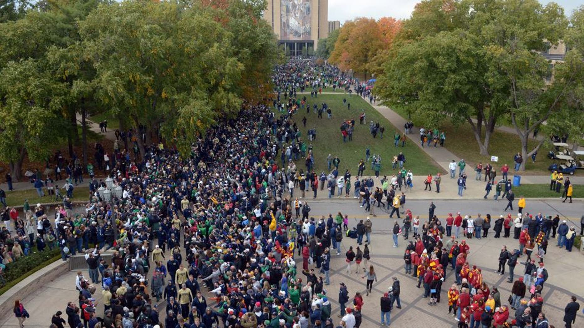 Oct 19, 2013; South Bend, IN, USA; Notre Dame Fighting Irish coach Brian Kelly leads players into Notre Dame Stadium with the Hesburgh Library Word of Life Mural aka Touchdown Jesus before the game against the Southern California Trojans. Mandatory Credit: Kirby Lee-USA TODAY Sports