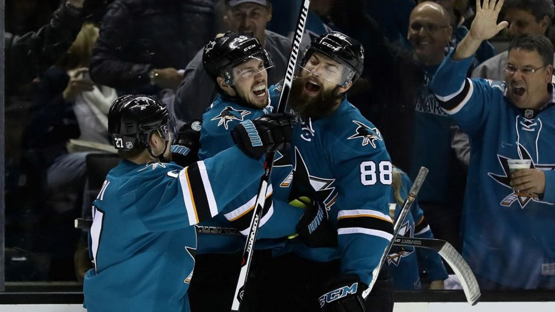 SAN JOSE, CA - MAY 12: Logan Couture #39 of the San Jose Sharks is congratulated by Brent Burns #88 and Joonas Donskoi #27 after Couture scored in the second period against the Nashville Predators in Game Seven of the Western Conference Second Round during the 2016 NHL Stanley Cup Playoffs at SAP Center on May 12, 2016 in San Jose, California. (Photo by Ezra Shaw/Getty Images)