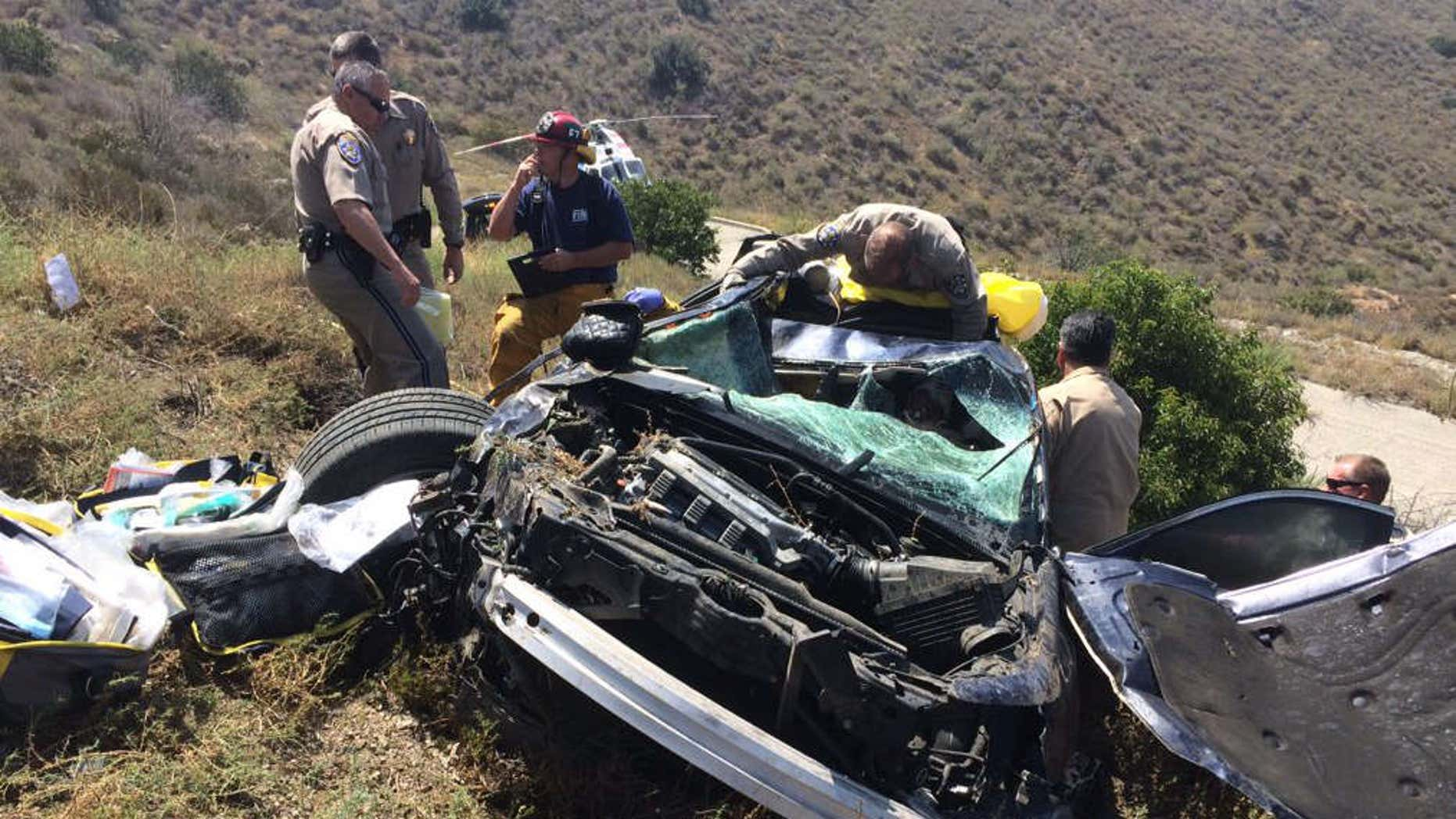 Photo shows fire officials extricating woman from crashed vehicle.