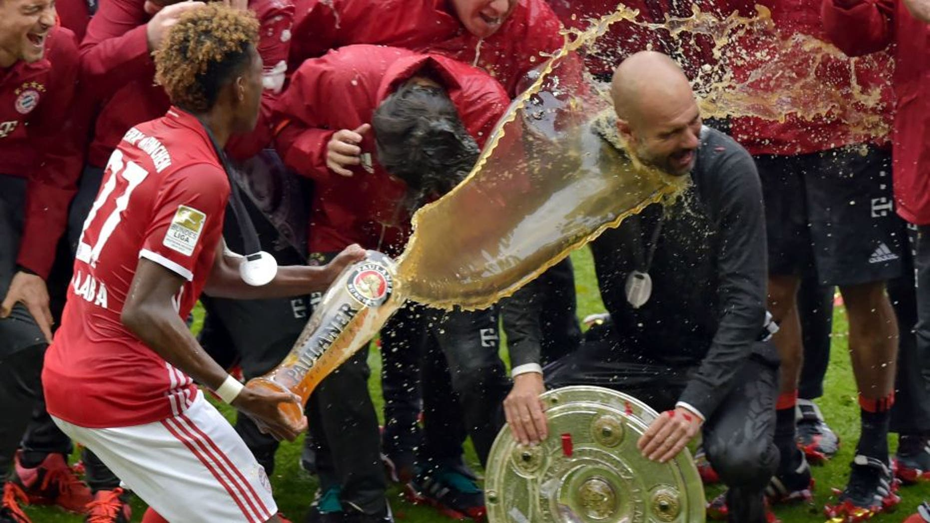 Bayern Munich's Spanish head coach Pep Guardiola (R) is doused in beer by Bayern Munich's Austrian midfielder David Alaba (L) celebrating their Bundesliga title after the German first division Bundesliga football match between FC Bayern Munich and Hannover 96 in Munich, southern Germany, on May 14, 2016. Bayern Munich won the German league for a record 4th time in a row. / AFP / GUENTER SCHIFFMANN / RESTRICTIONS: DURING MATCH TIME: DFL RULES TO LIMIT THE ONLINE USAGE TO 15 PICTURES PER MATCH AND FORBID IMAGE SEQUENCES TO SIMULATE VIDEO. == RESTRICTED TO EDITORIAL USE == FOR FURTHER QUERIES PLEASE CONTACT DFL DIRECTLY AT + 49 69 650050 (Photo credit should read GUENTER SCHIFFMANN/AFP/Getty Images)