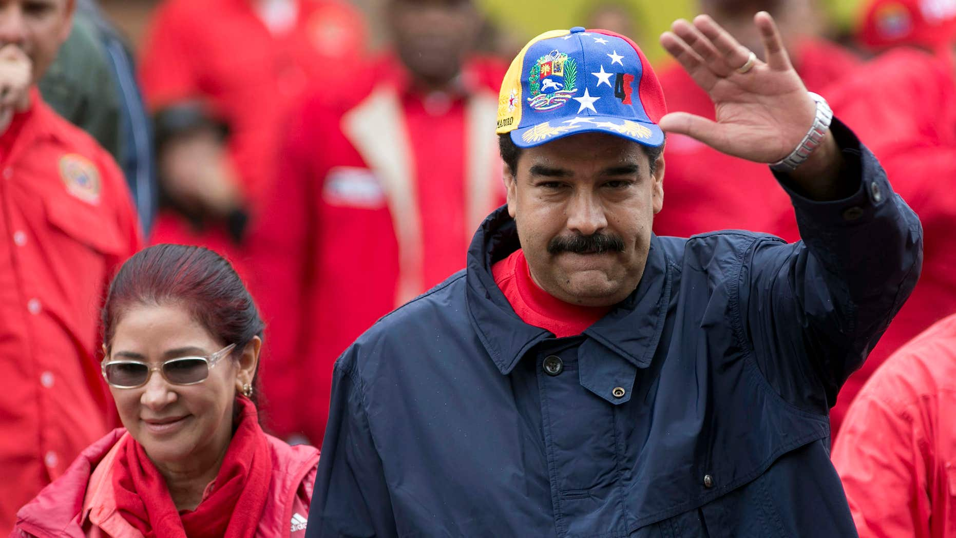 FILE - In this May 1, 2016 file photo, Venezuela's President Nicolas Maduro waves to supporters alongside first lady Cilia Flores during a labor day march in Caracas, Venezuela.