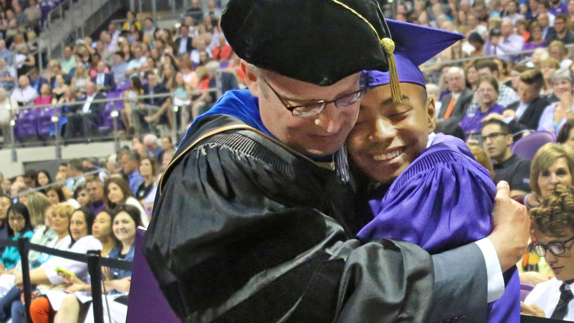 Fourteen year old Carson Huey-You gets a hug from his mentor, physics professor Magnus Rittby, after receiving a bachelor's degree in physics at the Texas Christian University commencement held in Fort Worth on Saturday, May 13, 2017.