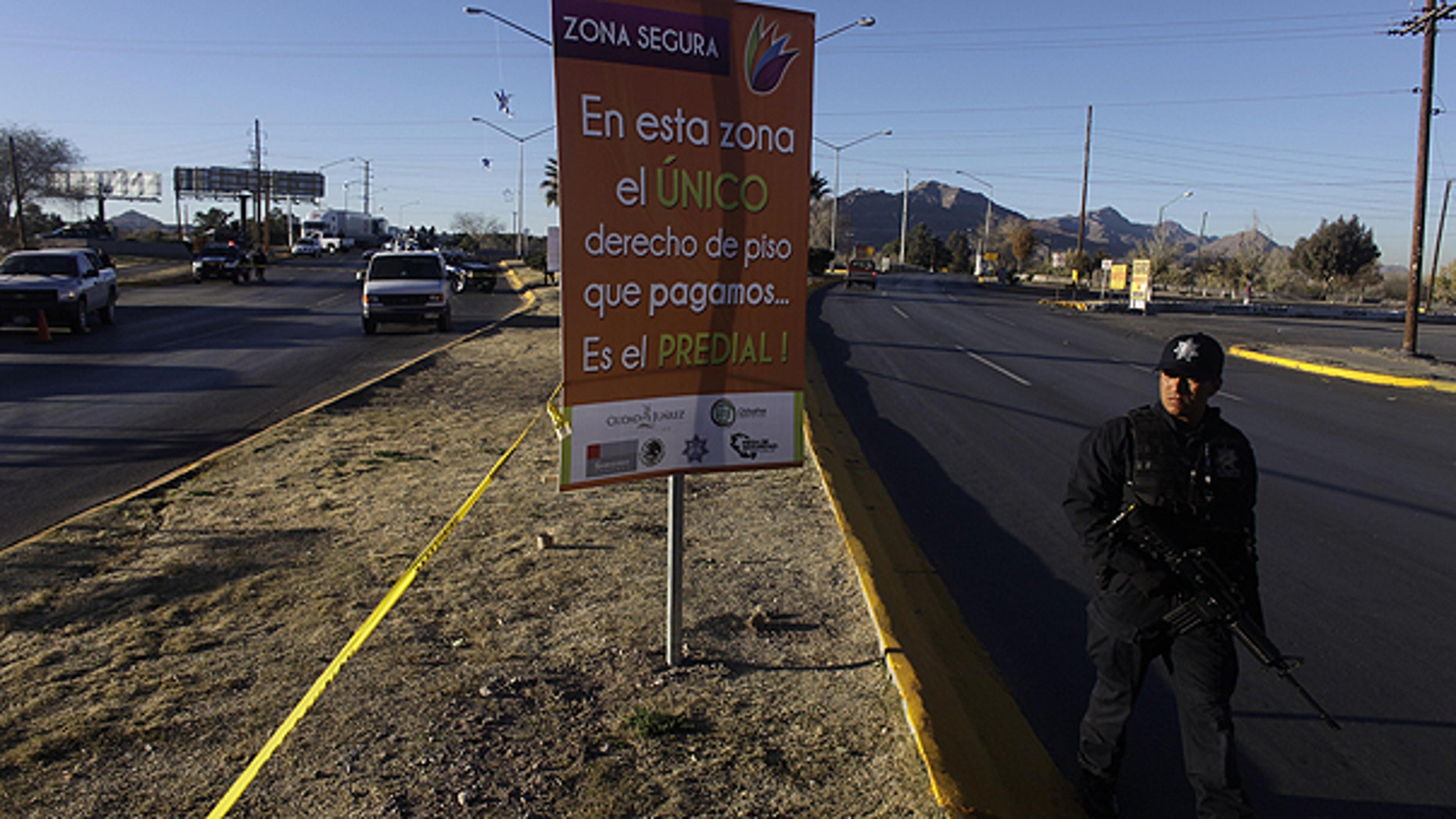 In this Dec. 13, 2010 file photo, a police officer walks beside a cordon for a crime scene in a heavily guarded commercial 'safe' zone in Ciudad Juarez, Mexico.