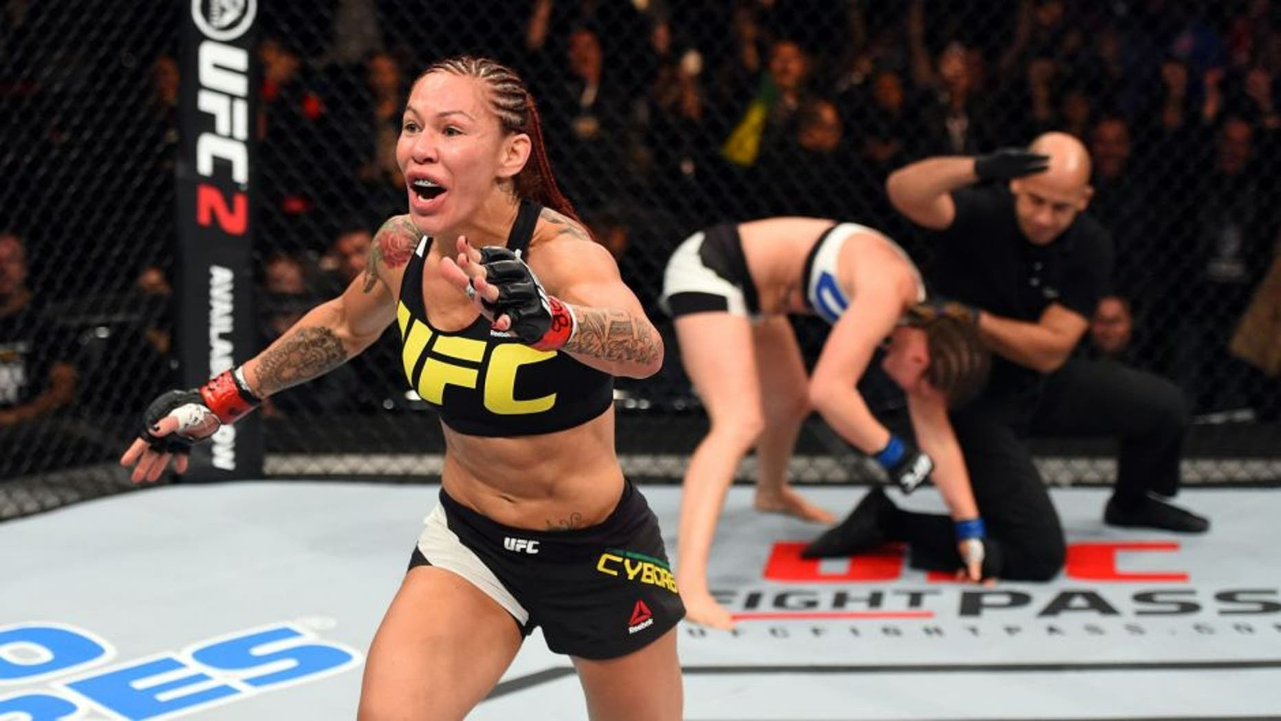 CURITIBA, BRAZIL - MAY 14: (L-R) Cristiane 'Cyborg' Justino of Brazil celebrates after defeating Leslie Smith in their women's catchweight bout during the UFC 198 event at Arena da Baixada stadium on May 14, 2016 in Curitiba, Parana, Brazil. (Photo by Josh Hedges/Zuffa LLC/Zuffa LLC via Getty Images)