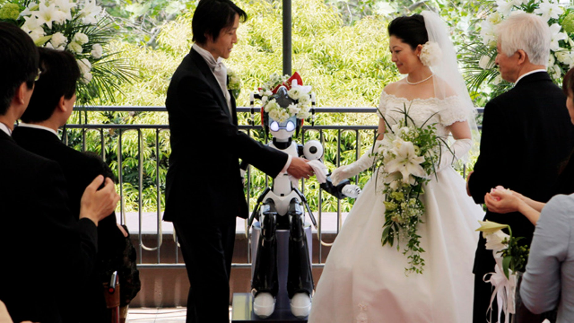 May 16: The 'I-Fairy' wears a wreath of flowers as it directs a wedding ceremony for groom Tomohiro Shibata 42, and bride Satoko Inouye, 36, at a Tokyo restaurant.