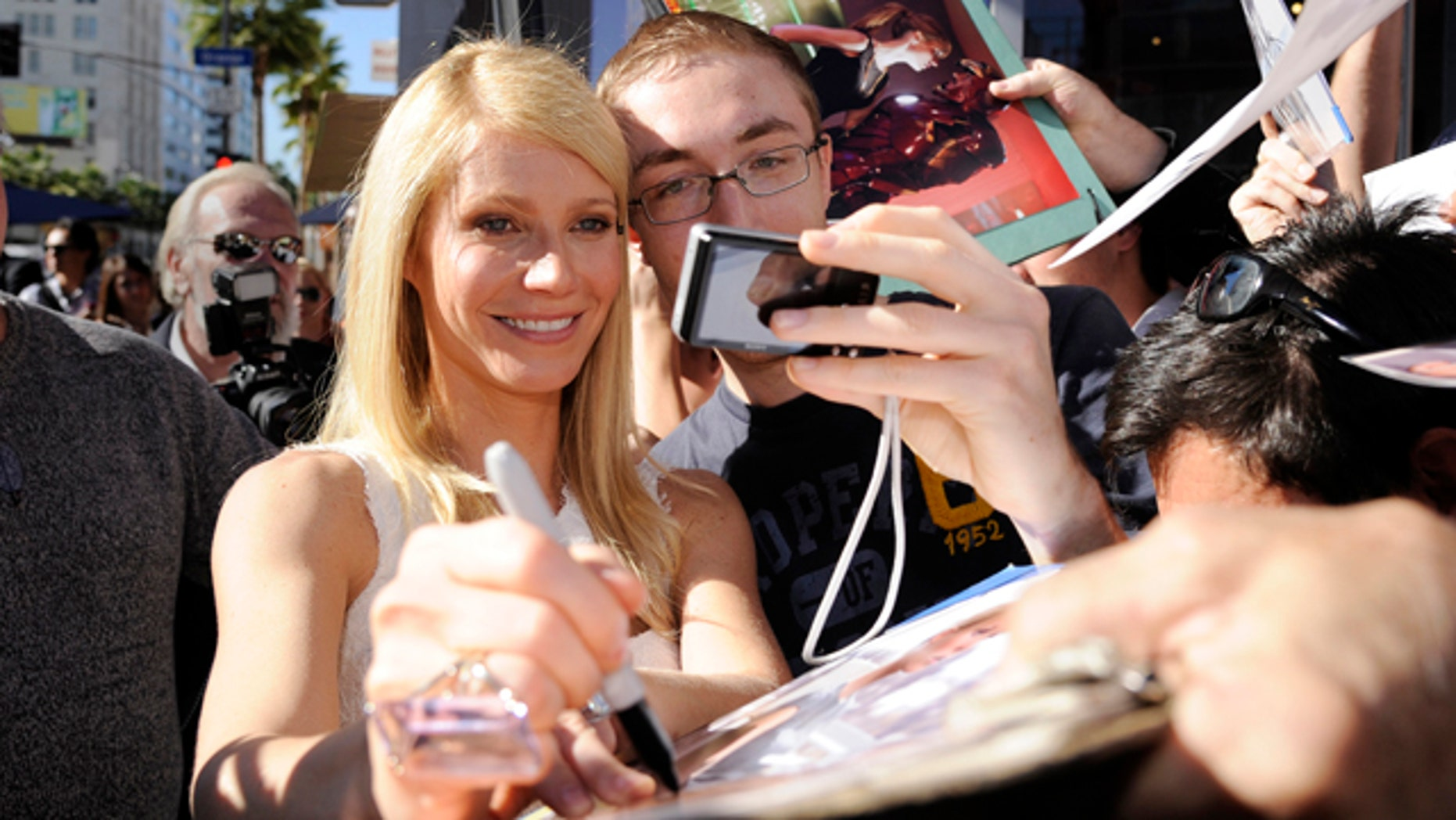Gwyneth Paltrow signs autographs following a ceremony where the actress received a star on the Hollywood Walk of Fame in Los Angeles December 13, 2010. REUTERS/Phil McCarten