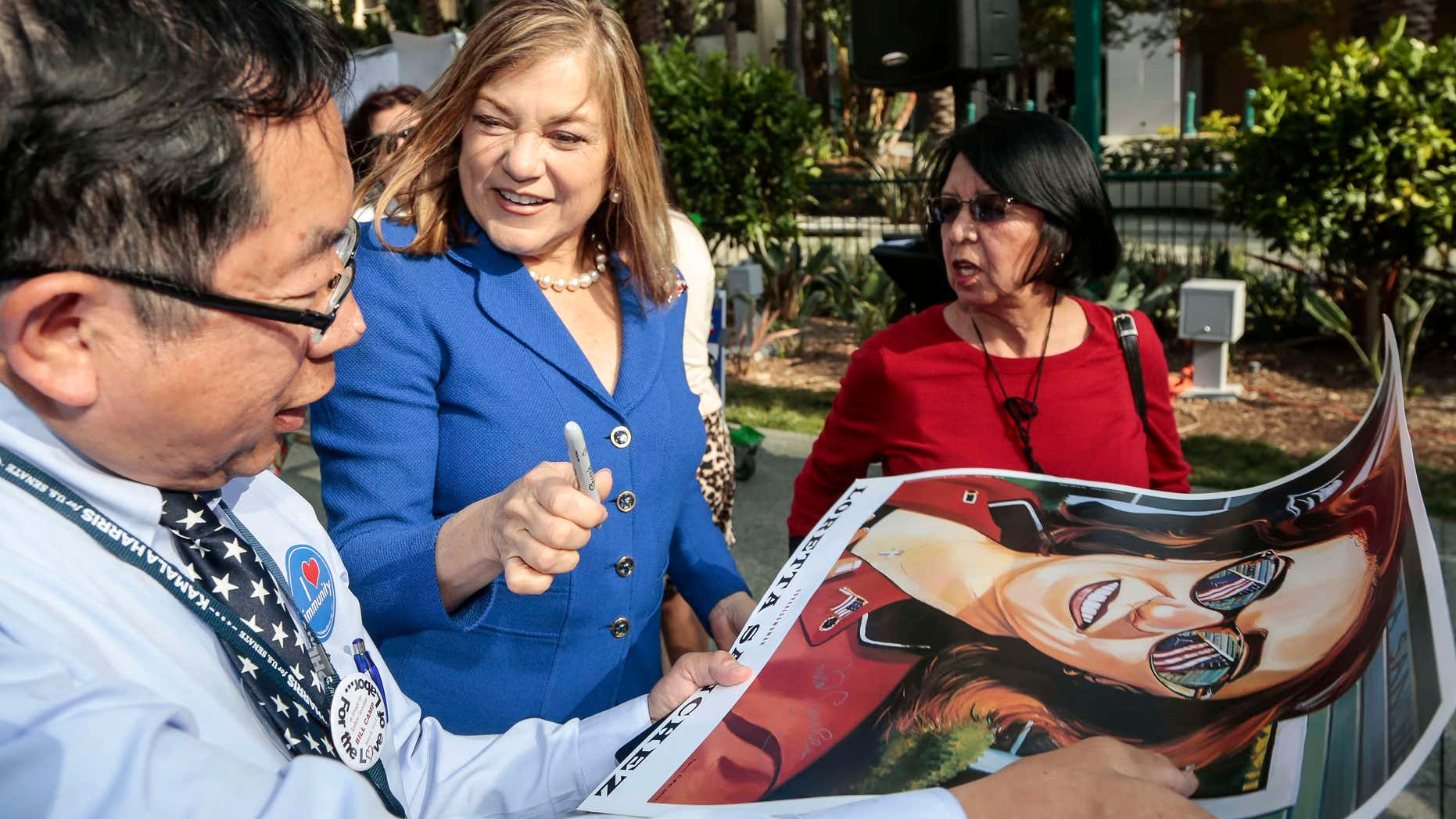 May 16, 2015: California Rep. Loretta Sanchez, second from left, autographs a California Senate race campaign poster to an unidentified supporter at the California Democrats State Convention in Anaheim, Calif.