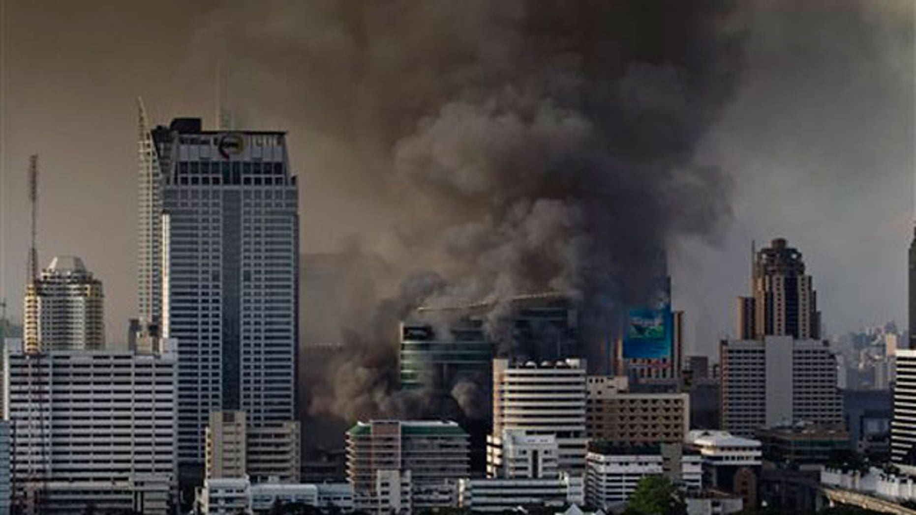 May 19: Smoke rises from burning fires in downtown Bangkok, Thailand, following the surrender of anti-government leaders to the police.