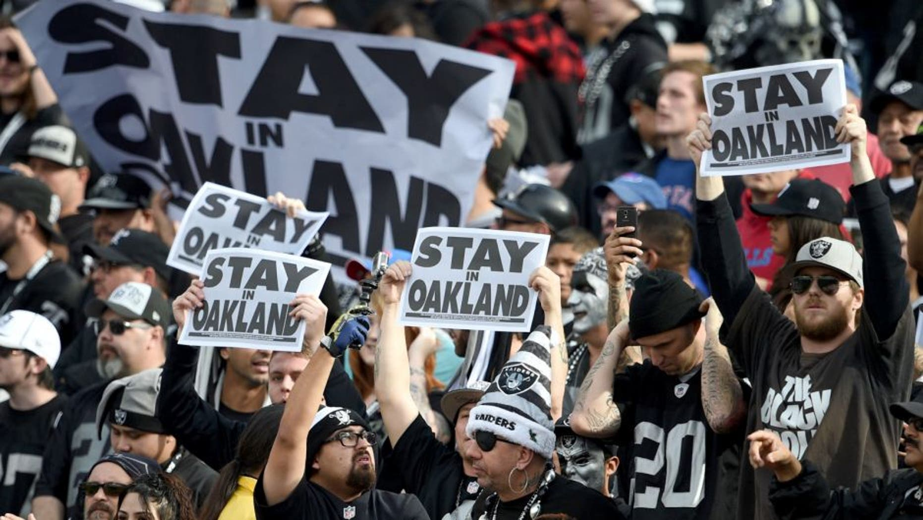 December 21, 2014; Oakland, CA, USA; Oakland Raiders fans hold up signs before the game against the Buffalo Bills at O.co Coliseum. Mandatory Credit: Kyle Terada-USA TODAY Sports