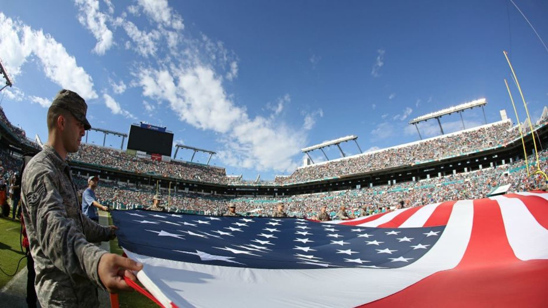 of the game at Sun Life Stadium on November 22, 2015 in Miami Gardens, Florida.,MIAMI GARDENS, FL - NOVEMBER 22: Memebers of the US Armed Forces hold an American Flag on the field for the singing of God Bless America during the second quarter of the game between the Miami Dolphins and the Dallas Cowboys at Sun Life Stadium on November 22, 2015 in Miami Gardens, Florida. (Photo by Rob Foldy/Getty Images)