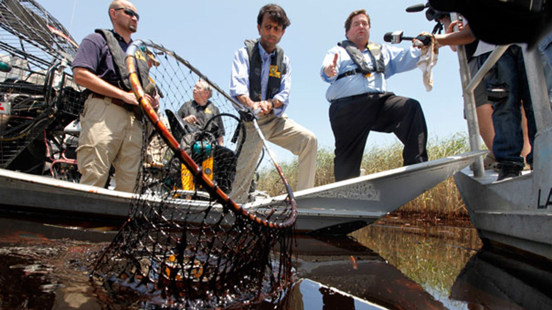 May. 19: Louisiana Gov. Bobby Jindal, center, and Plaquemines Parish President Billy Nungesser, right, tour the oil impacted marsh of Pass a Loutre, La.