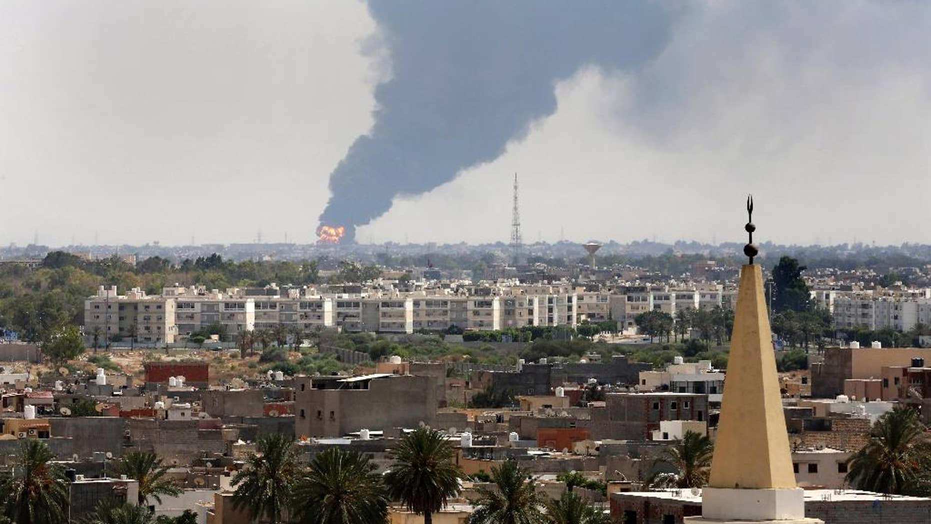 """Black smoke billows over the skyline as a fire at the oil depot for the airport rages out of control after being struck in the crossfire of warring militias battling for control of the airfield, in Tripoli, Libya Monday, July 28, 2014. The latest violence to plague the country has so far killed scores of people and wounded hundreds as foreigners flee the chaos. Libya's interim government said in a statement that the fire could trigger a """"humanitarian and environmental disaster"""" in Tripoli, appealing for """"international help"""" to extinguish the inferno. (AP Photo/Mohammed Ben Khalifa)"""