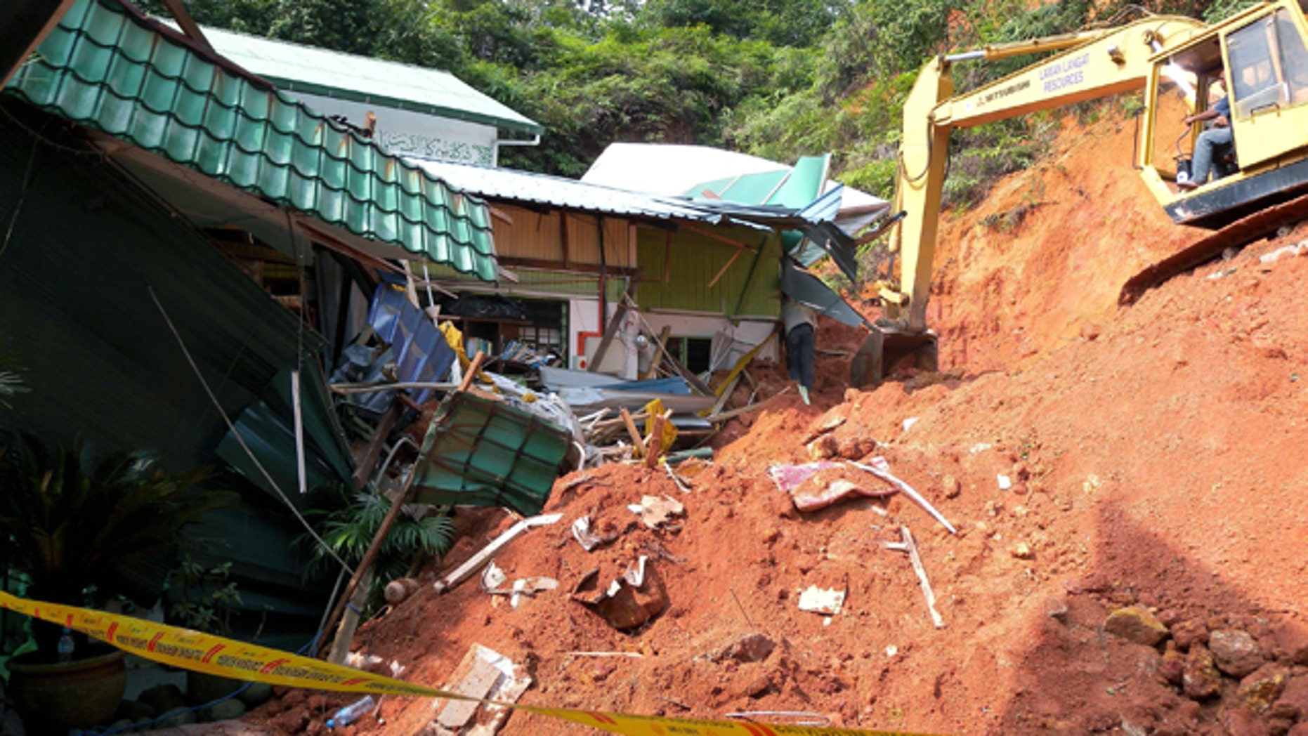 May 21: A rescuer uses a construction machine to search for the bodies believed to be buried by a landslide in Hulu Langat in central Selangor state, outside Kuala Lumpur, Malaysia.
