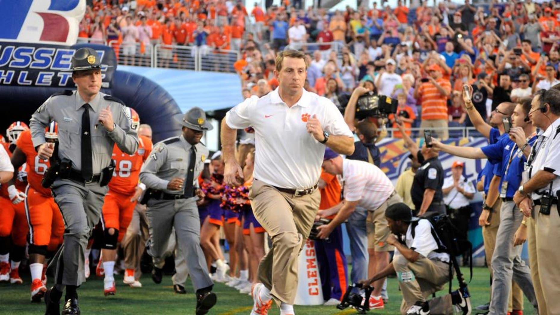 Dec 29, 2014; Orlando, FL, USA; Clemson Tigers head coach Dabo Swinney runs onto the field before the 2014 Russell Athletic Bowl at Florida Citrus Bowl. Mandatory Credit: David Manning-USA TODAY Sports
