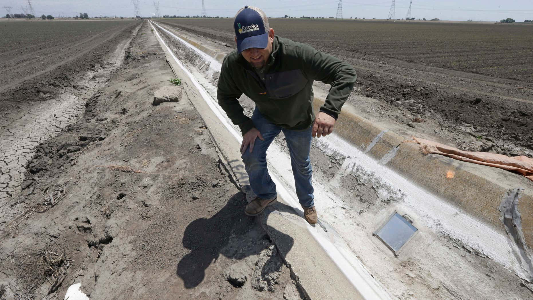 May 18, 2015: Farmer Gino Celli climbs out of a irrigation canal that is covered in dried salt on a field he farms near Stockton, Calif.