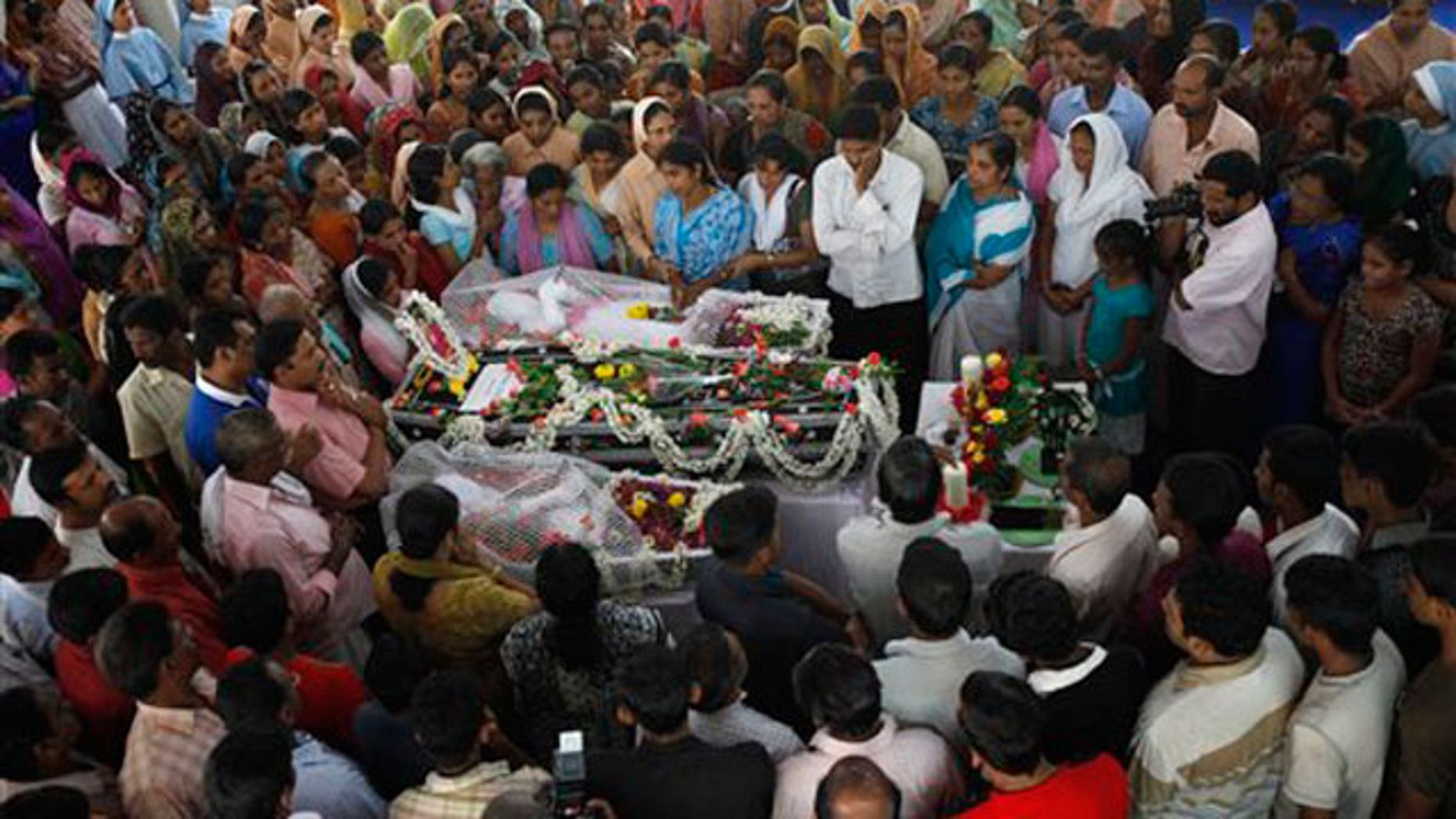 May 23: Relatives grieve next to the bodies of victims who died in an Air India Express plane crash in Mangalore, India.