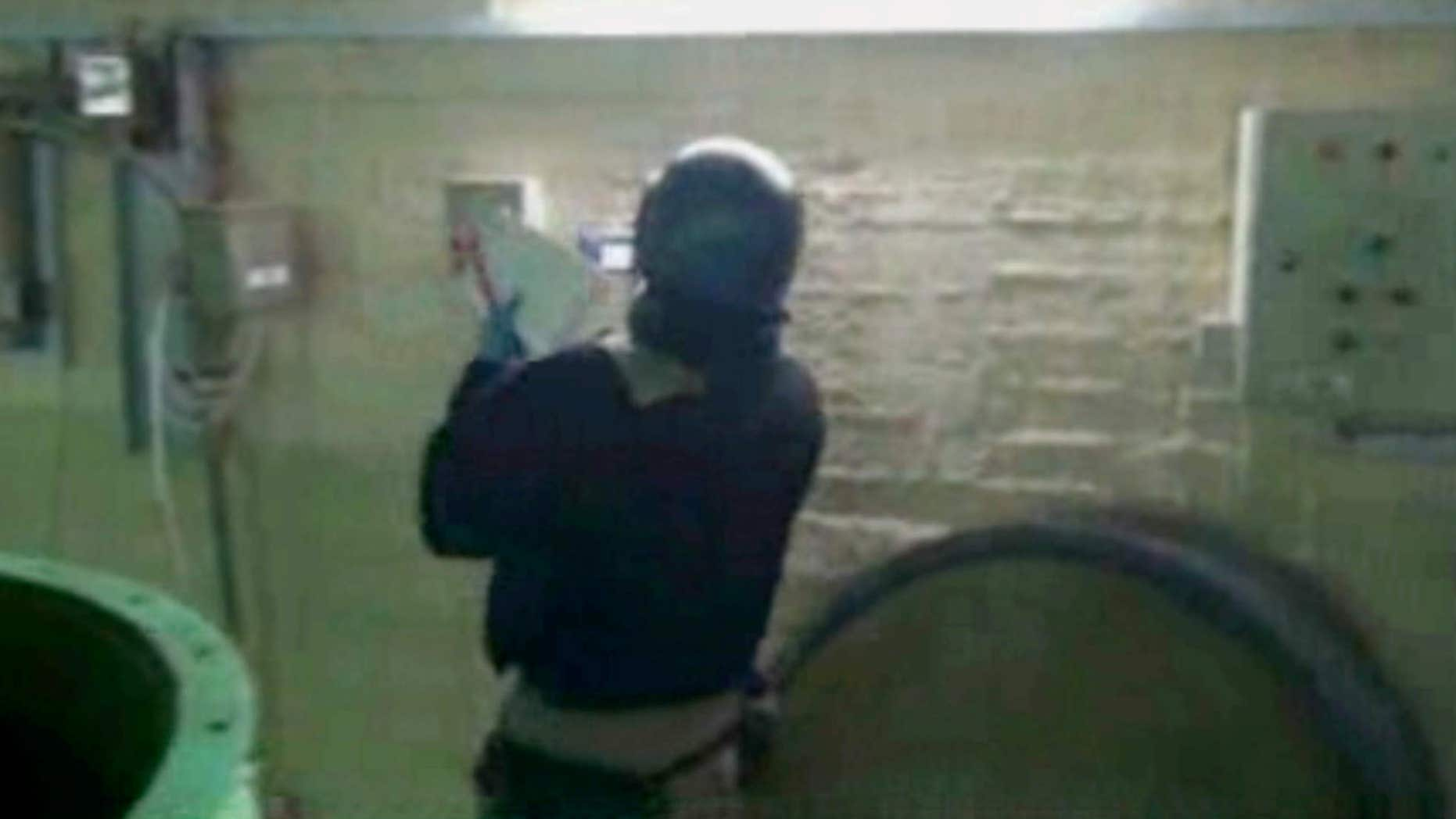 Oct. 8, 2013: This file image made from video broadcast on Syrian State Television, purports to show a chemical weapons expert taking samples at a chemical weapons plant at an unknown location in Syria.
