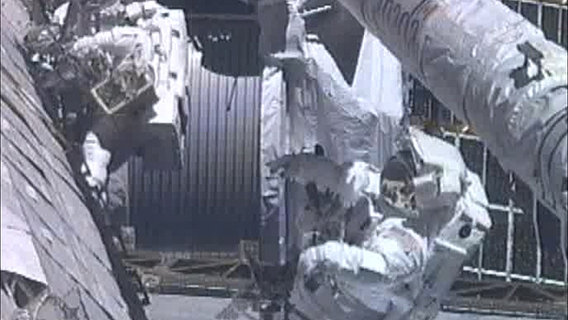 May 27: In this image from NASA television astronauts Greg Chamitoff , foreground, and Mike Fincke work outside the International Space Station repositioning the shuttle's Orbiter Boom Sensor System during the fourth spacewalk.