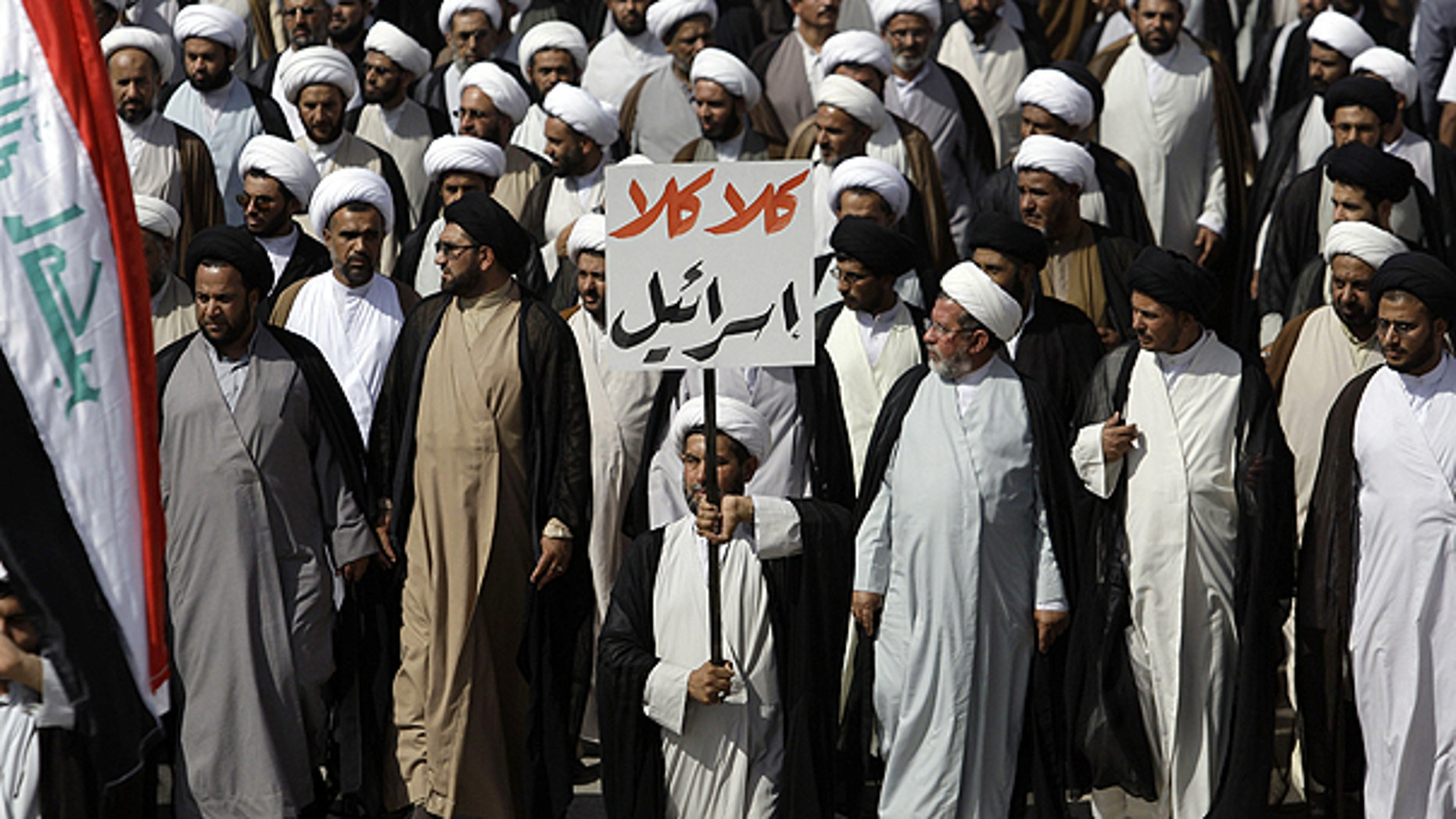 """May 26: Supporters of cleric Muqtada al-Sadr march while holding a sign that reads, """"no, no to Israel,"""" in Arabic, in the Sadr City district of Baghdad, Iraq."""