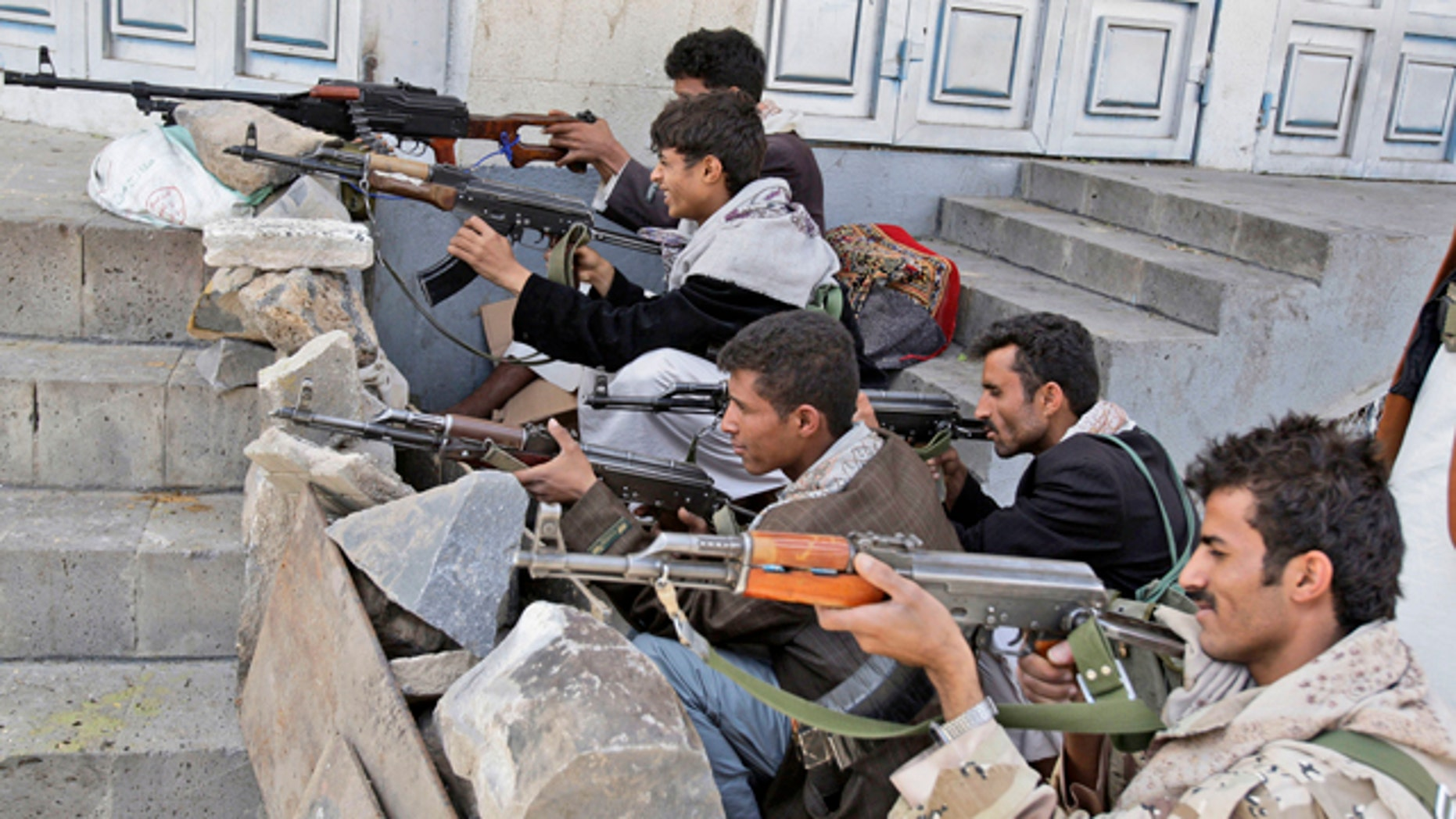 May 24: Tribesmen take positions next to the house of Sheik Sadeq al-Ahmar, the head of the powerful Hashid tribe, during clashes with Yemeni security forces in Sanaa, Yemen.